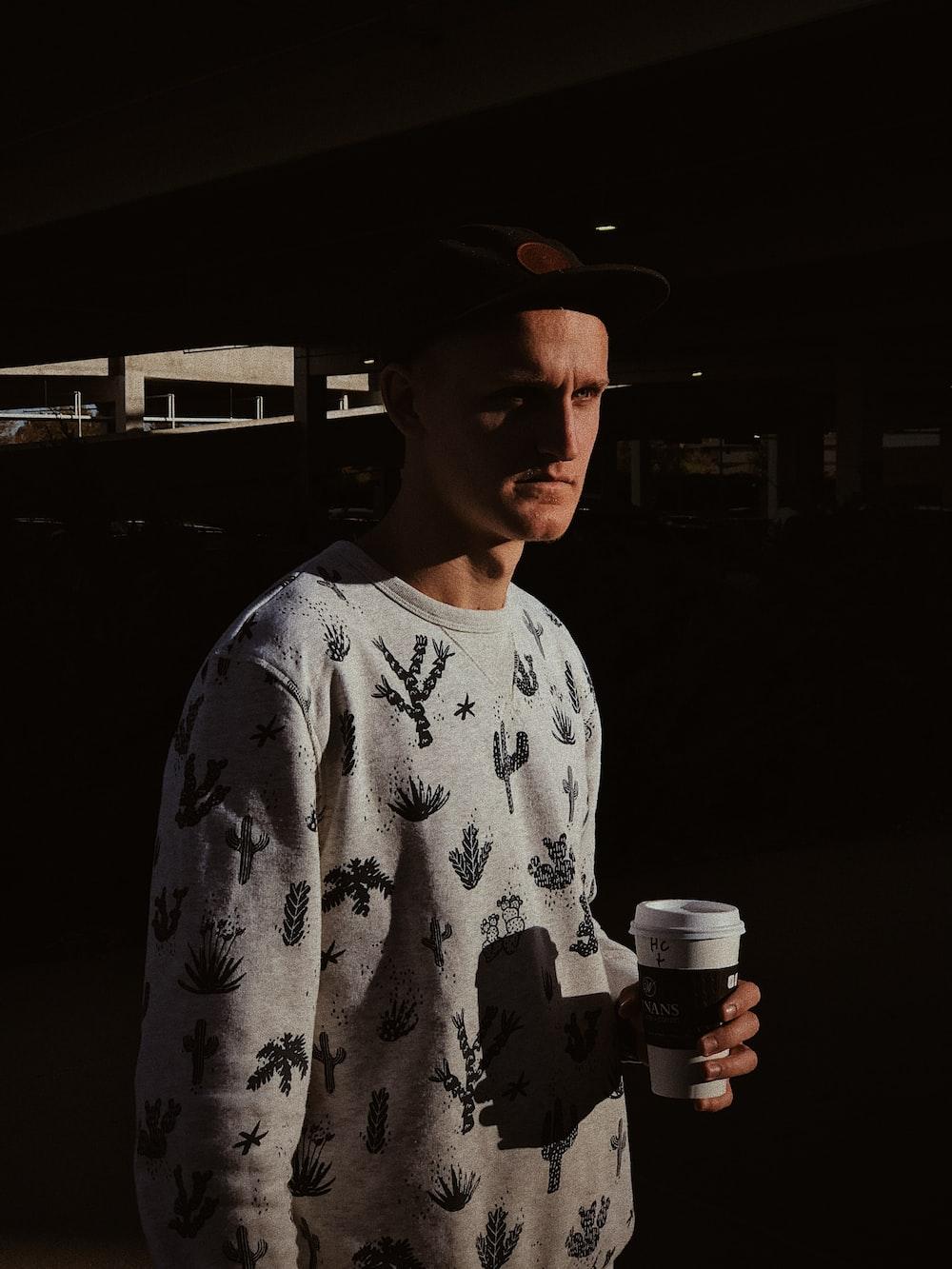 man wearing grey sweatshirt holding cup