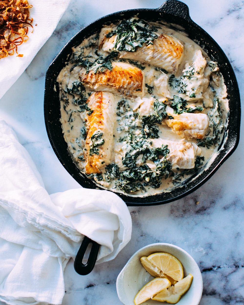 Cast Iron skillet with sauteed fish in a cream sauce with herbs