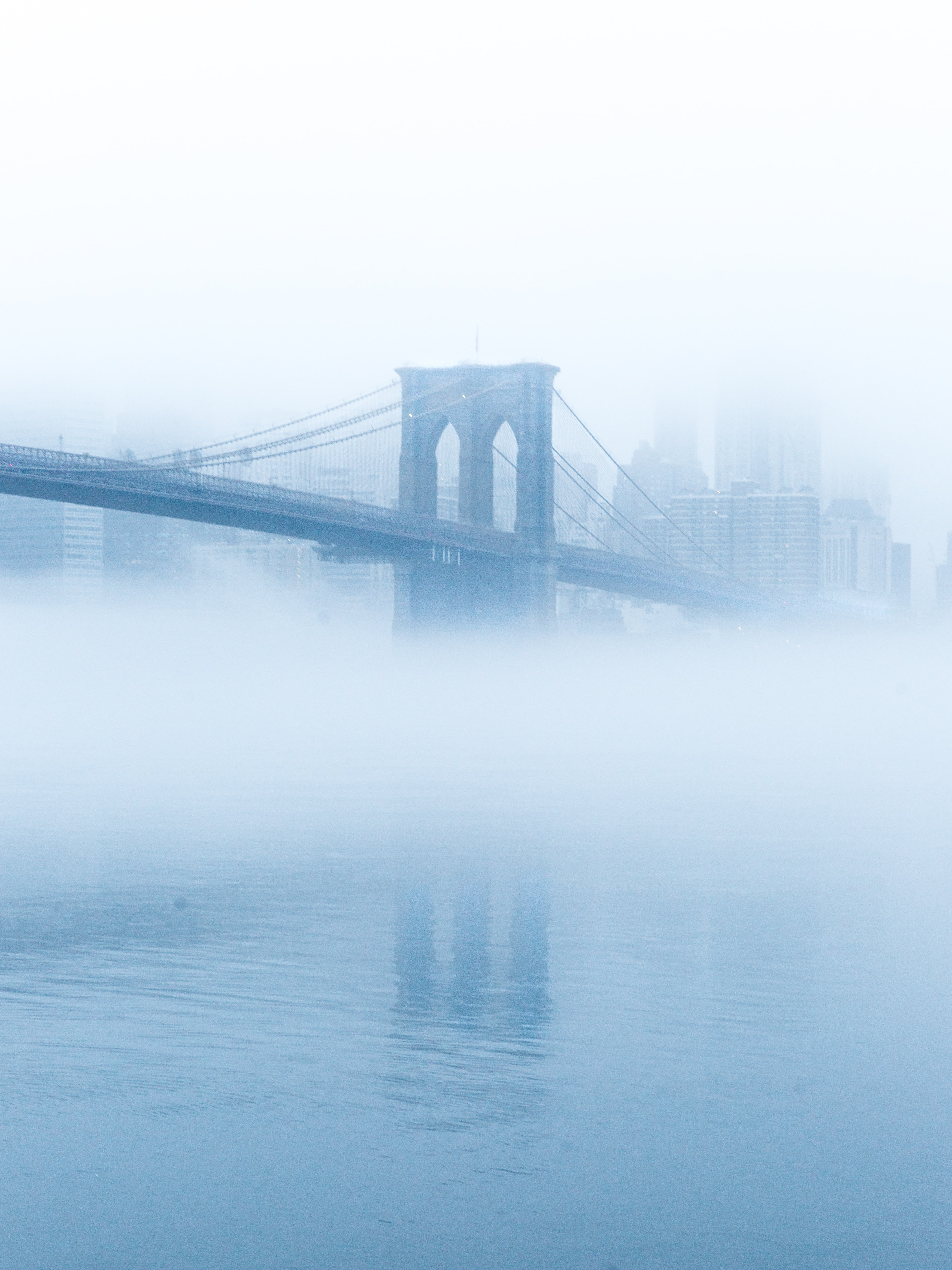 Soft blue fog circling Brooklyn Bridge