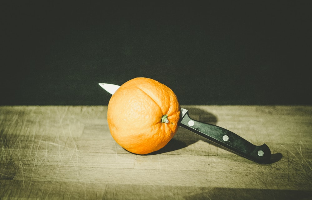 orange fruit and gray and black knife on brown wooden board low-light photography
