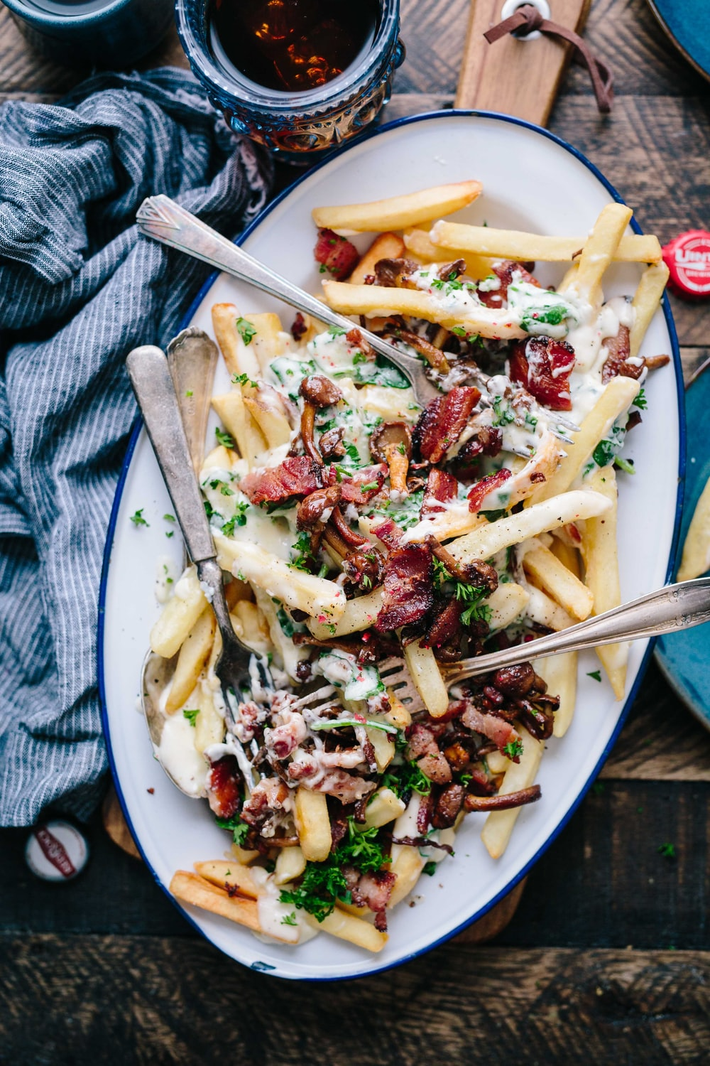 bacon strips and melted cheese topped fries on oval white and blue platter with gray stainless steel forks