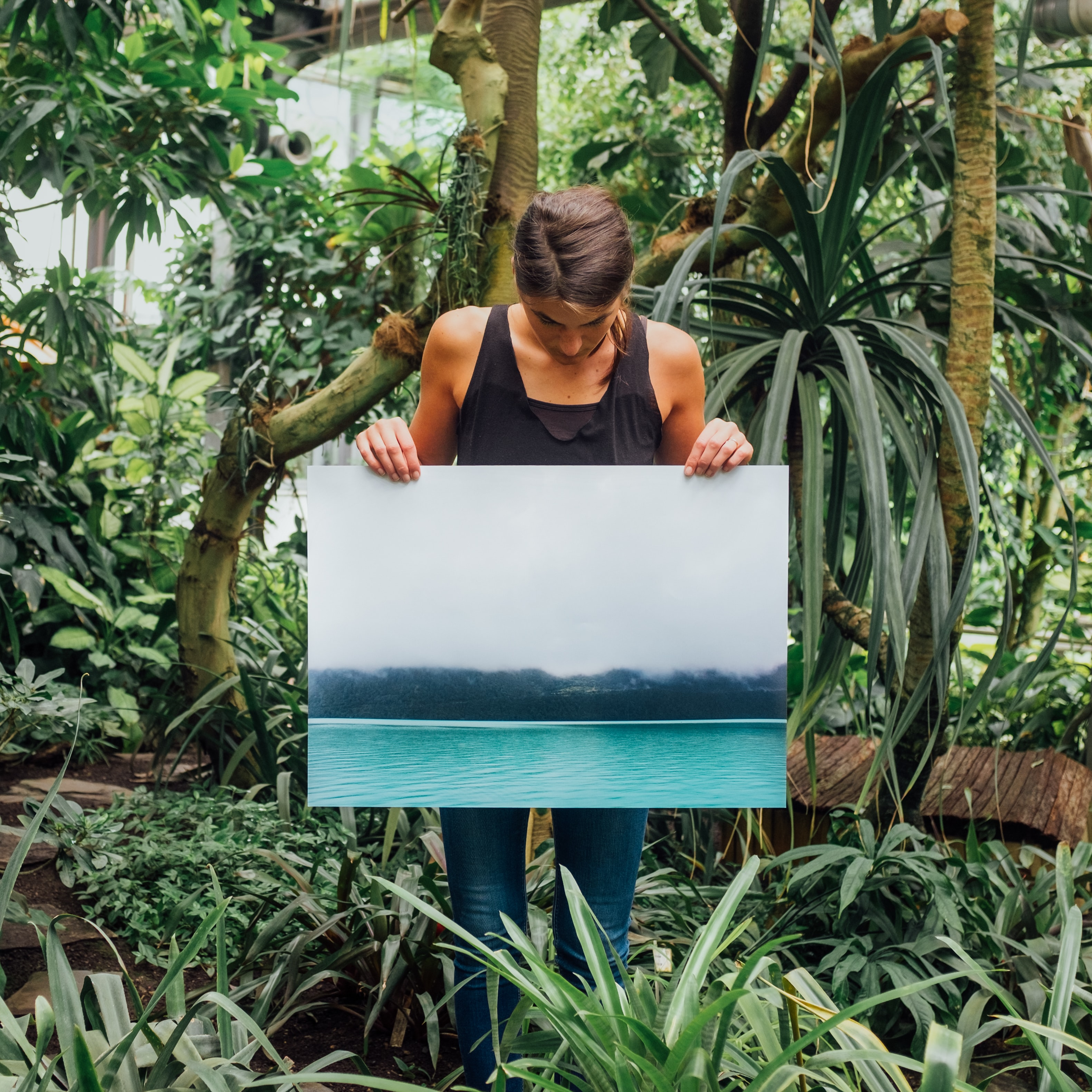 Artist holding a canvas print of a lake among rainforest trees