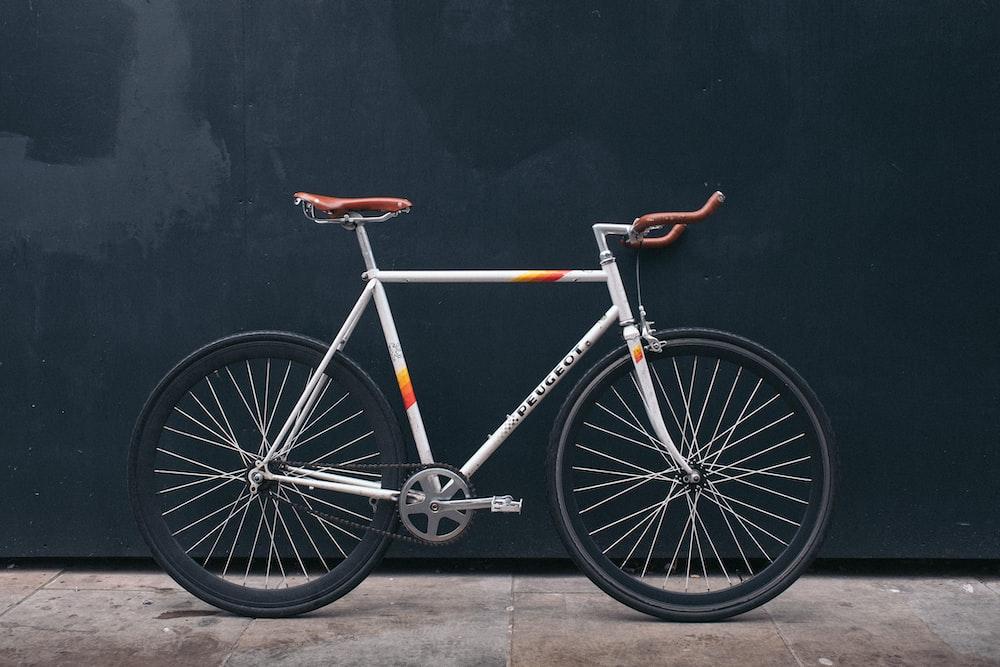 gray fixie bike leaning on black wall