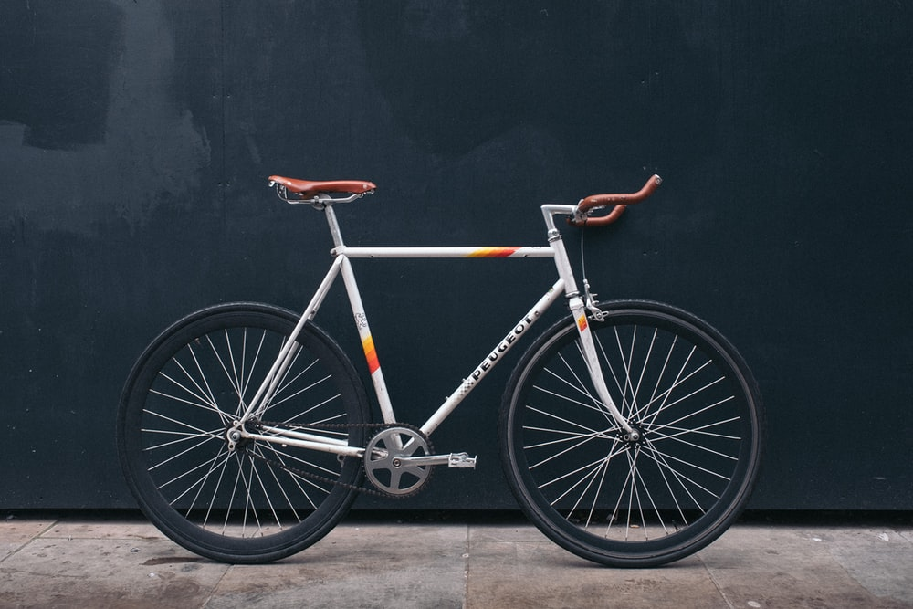 gray fixie bike leaning on black wall