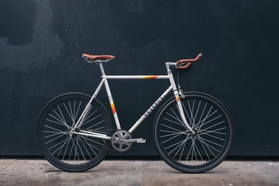 gray fixie bike leaning on black wall bike zoom background