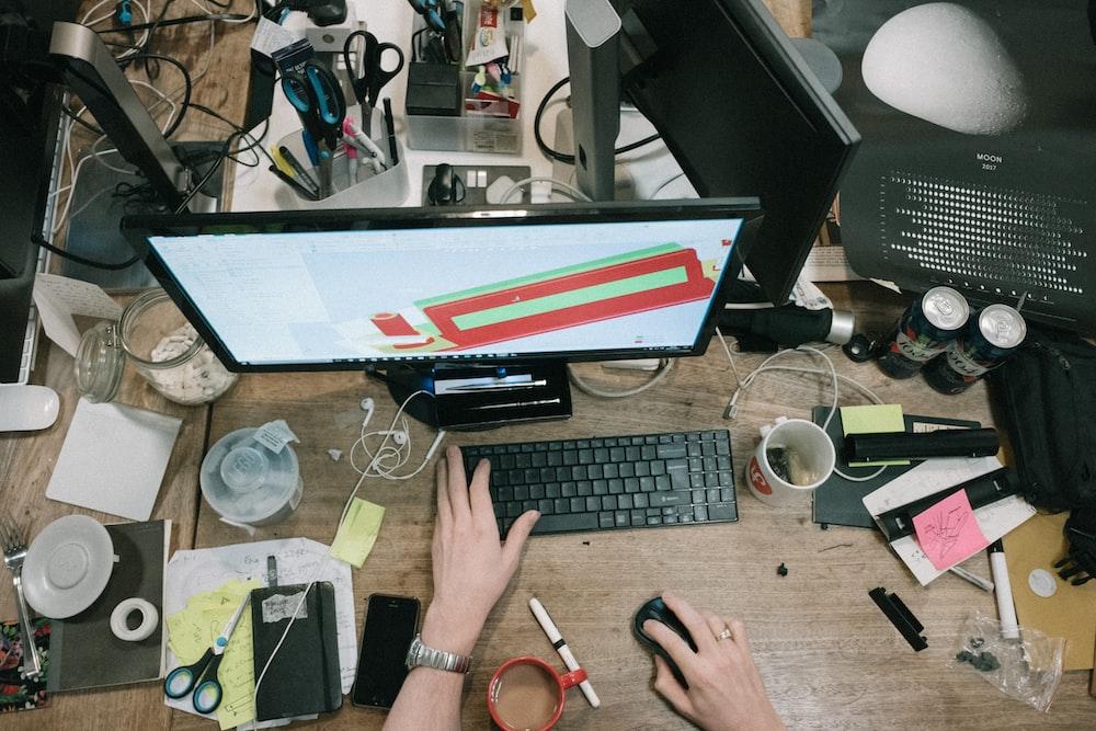 茶色の木製のテーブルにコンピューターを使用している人