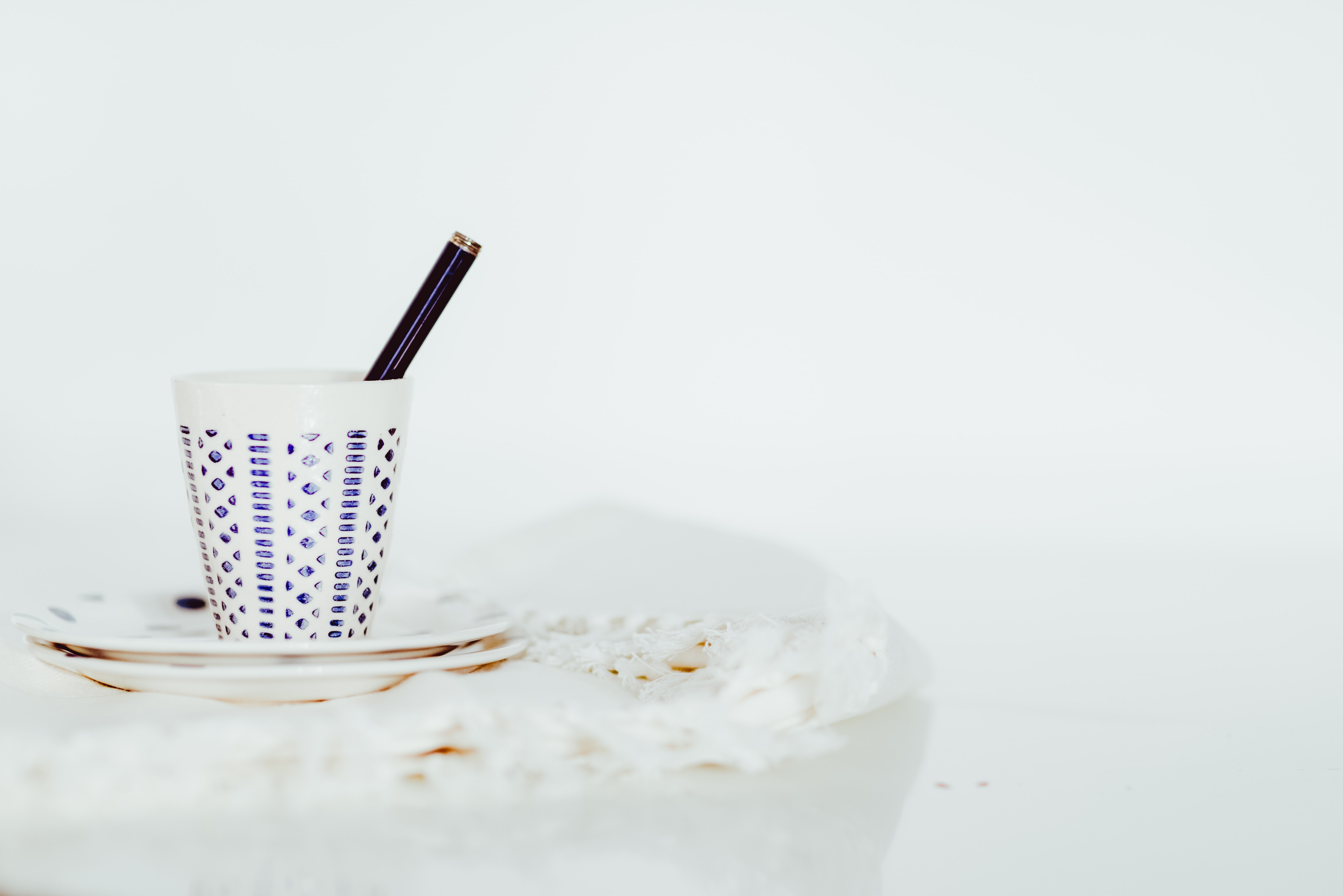 A pen in a white ceramic cup on a saucer against a white background