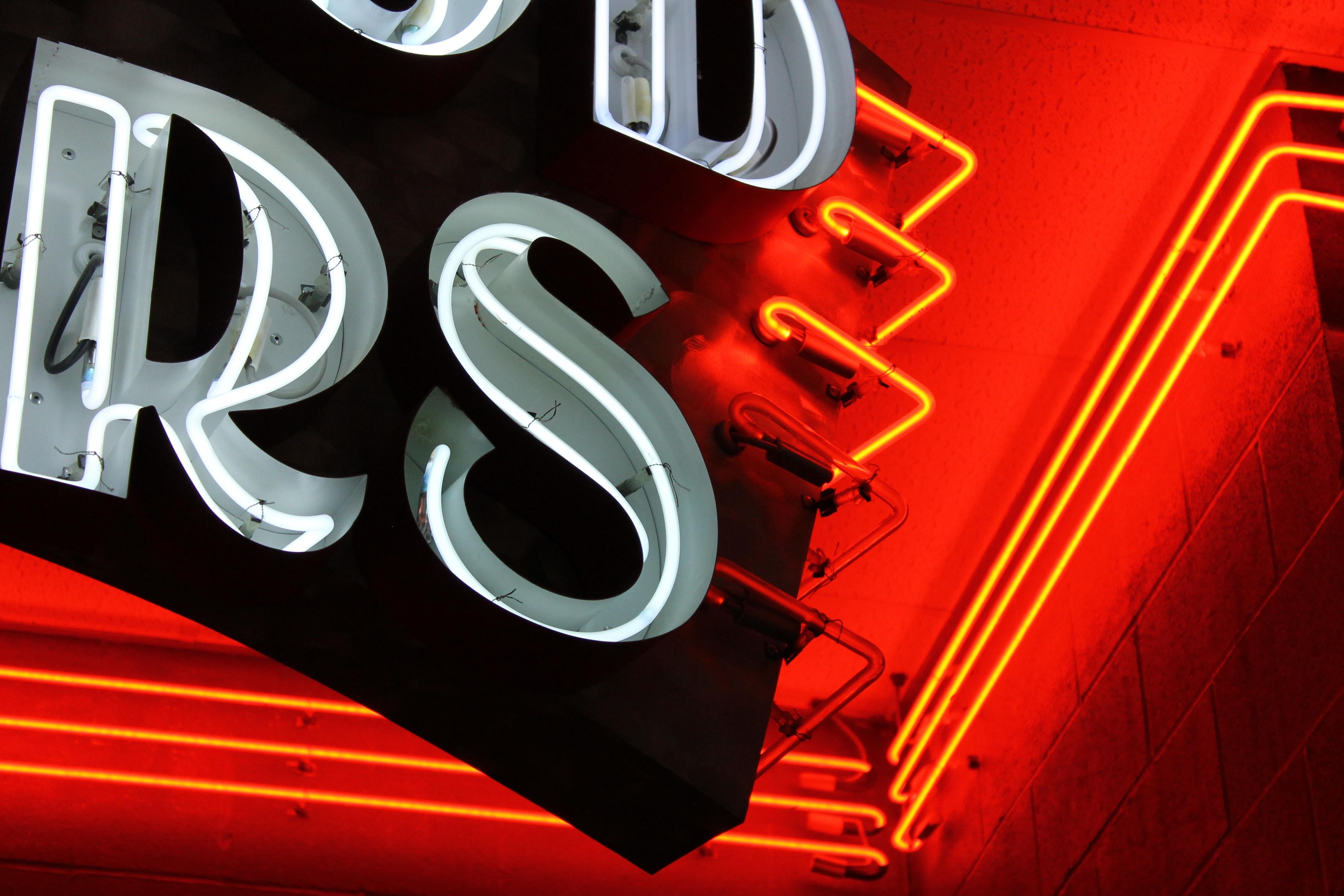 Details of lettering on vintage neon sign glowing orange