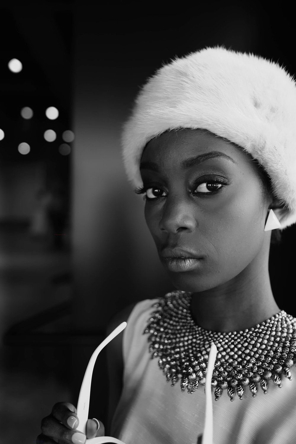 A black-and-white shot of a young woman in a furry cap