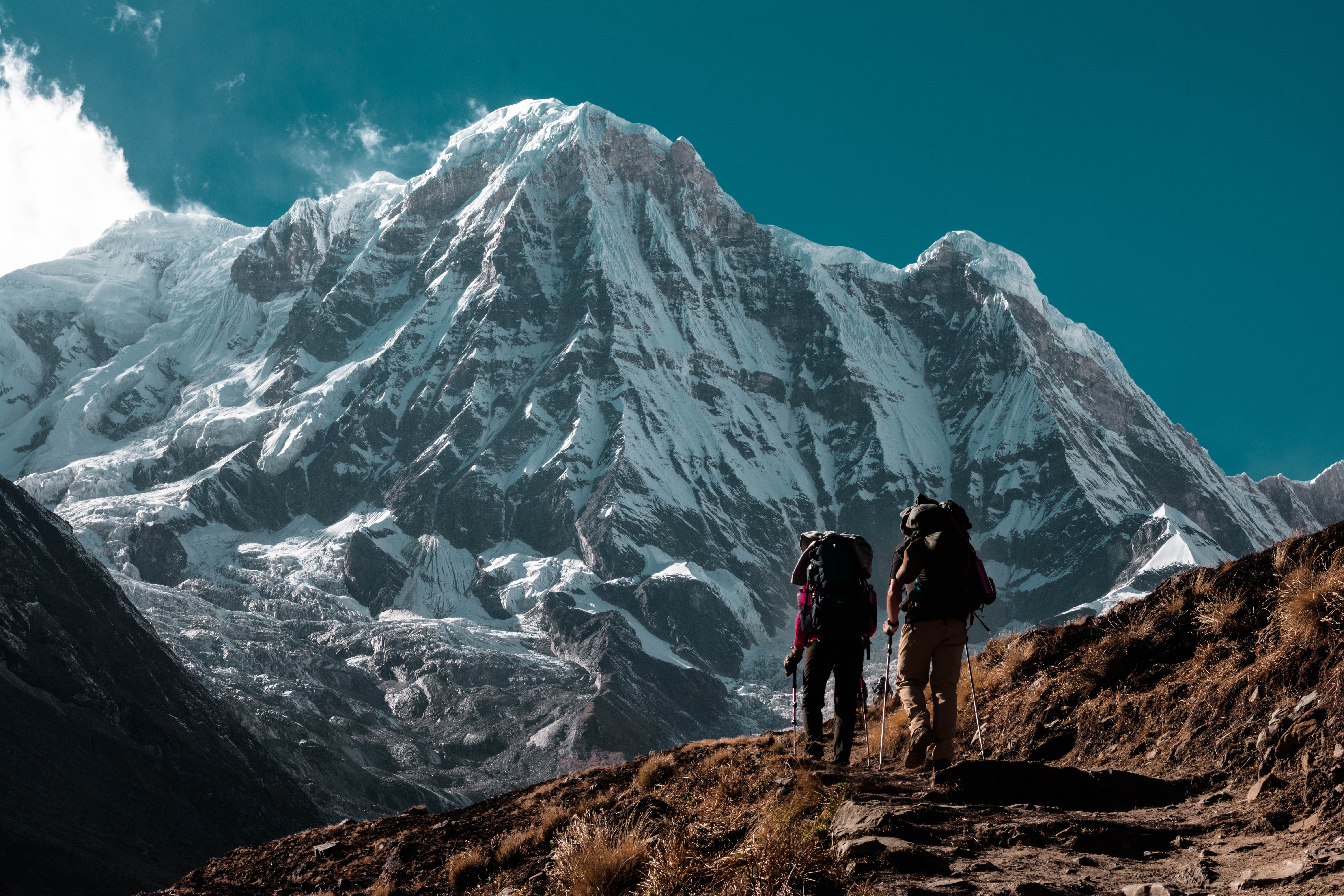 two person hiking near mountain range covered with snow