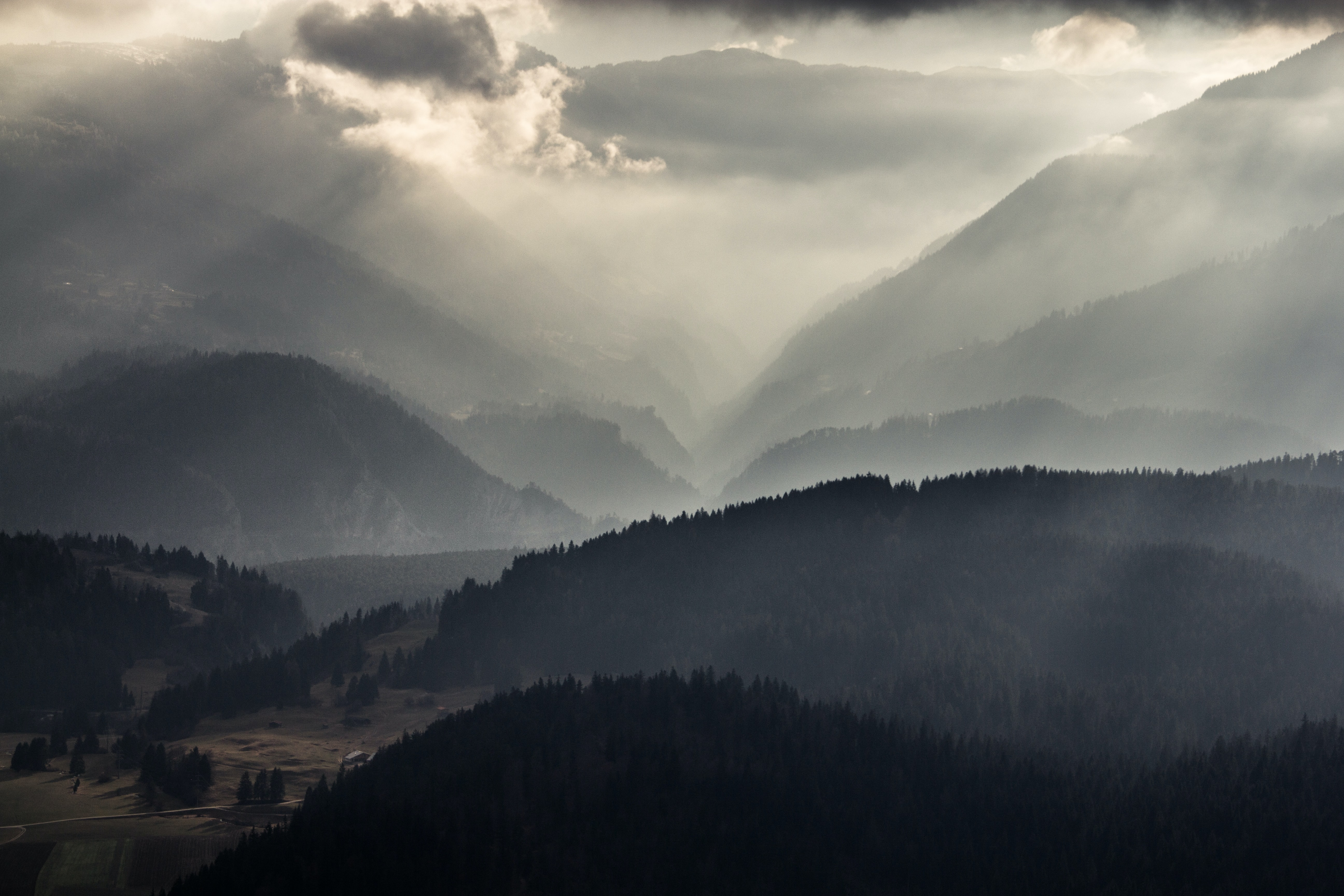 Sun breaking through clouds over a wooded valley
