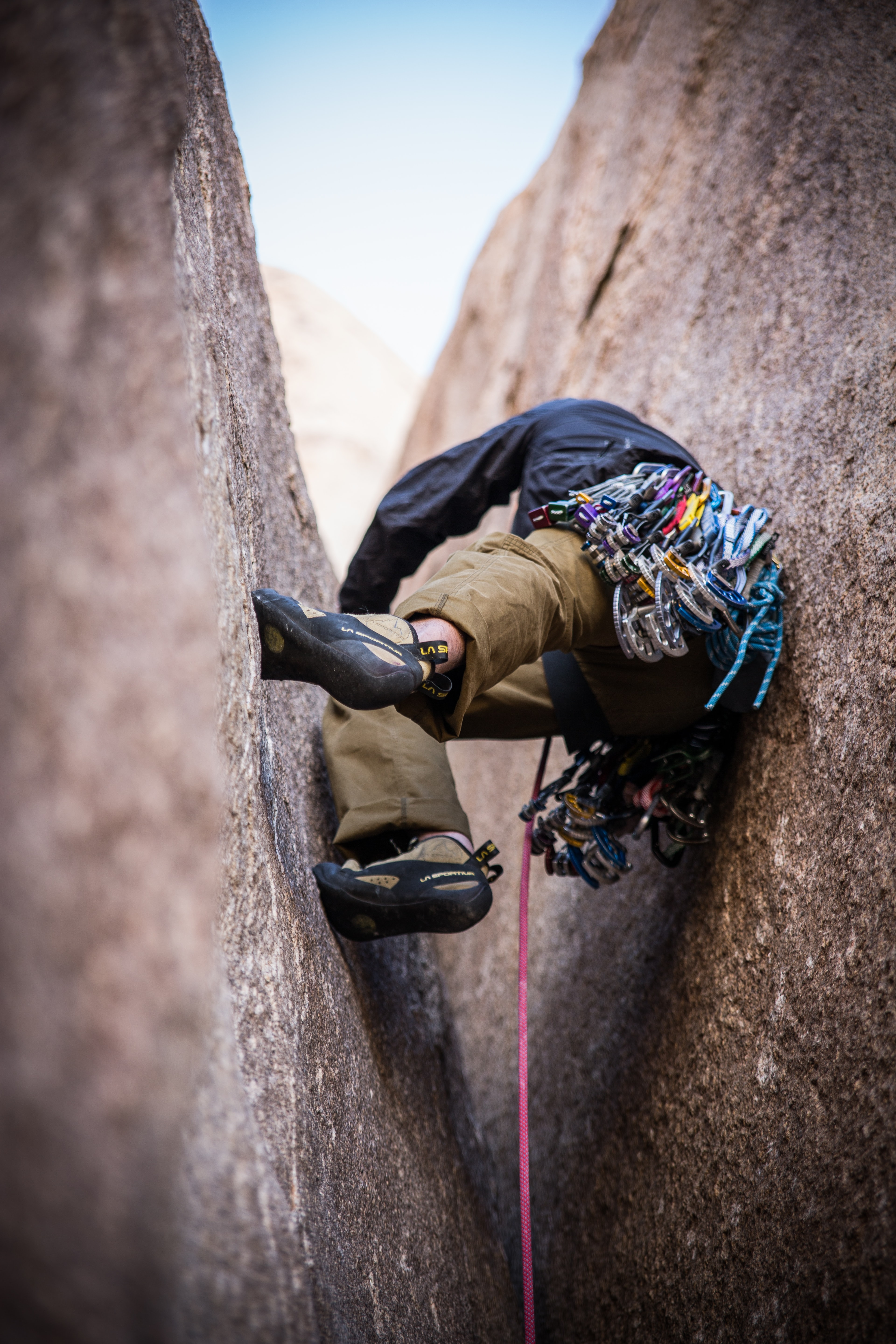 A rock climber scaling between two massive rocks and attached to a harness