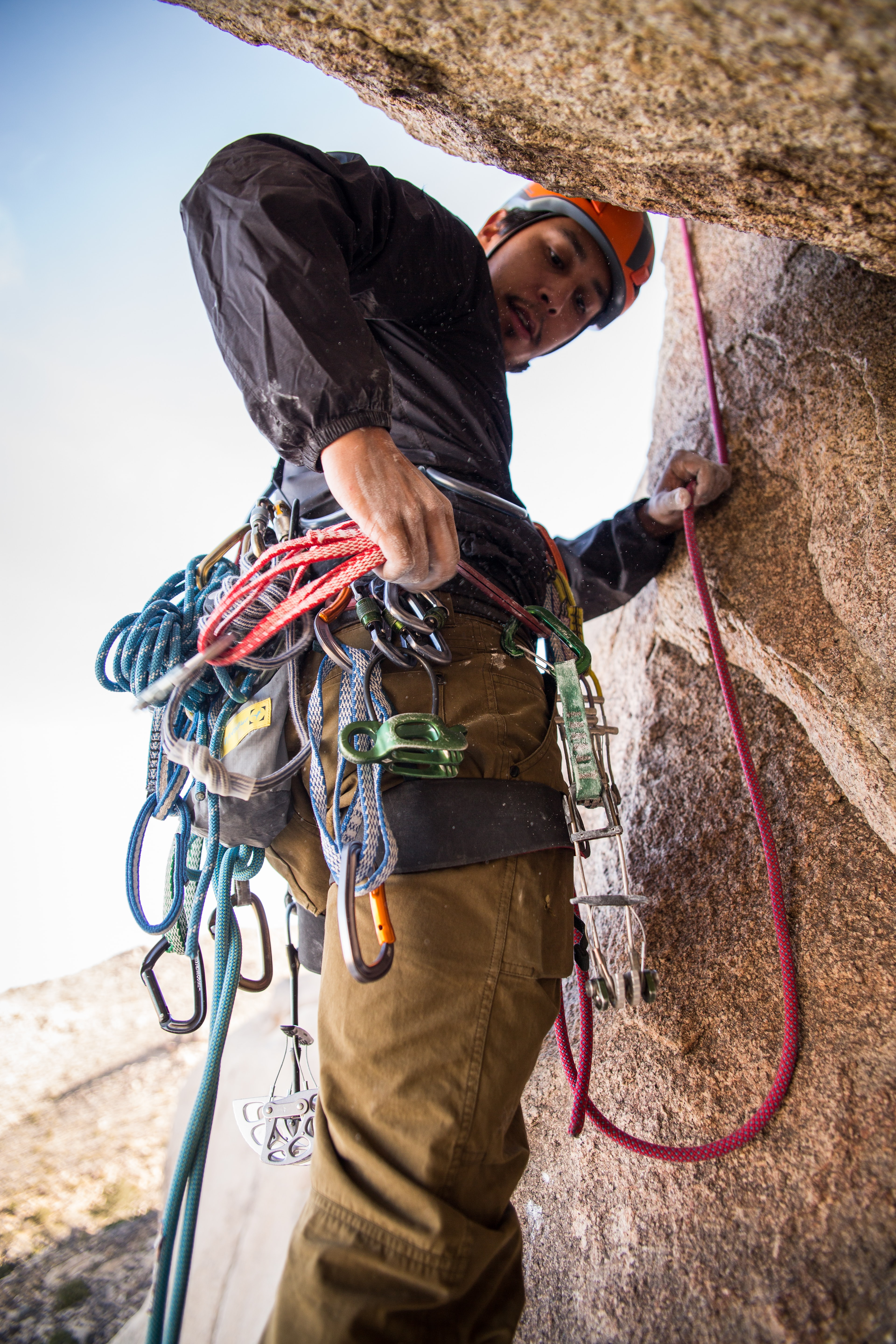 rock climber holding red rope strapped on waist while on side of brown boulder at daytime
