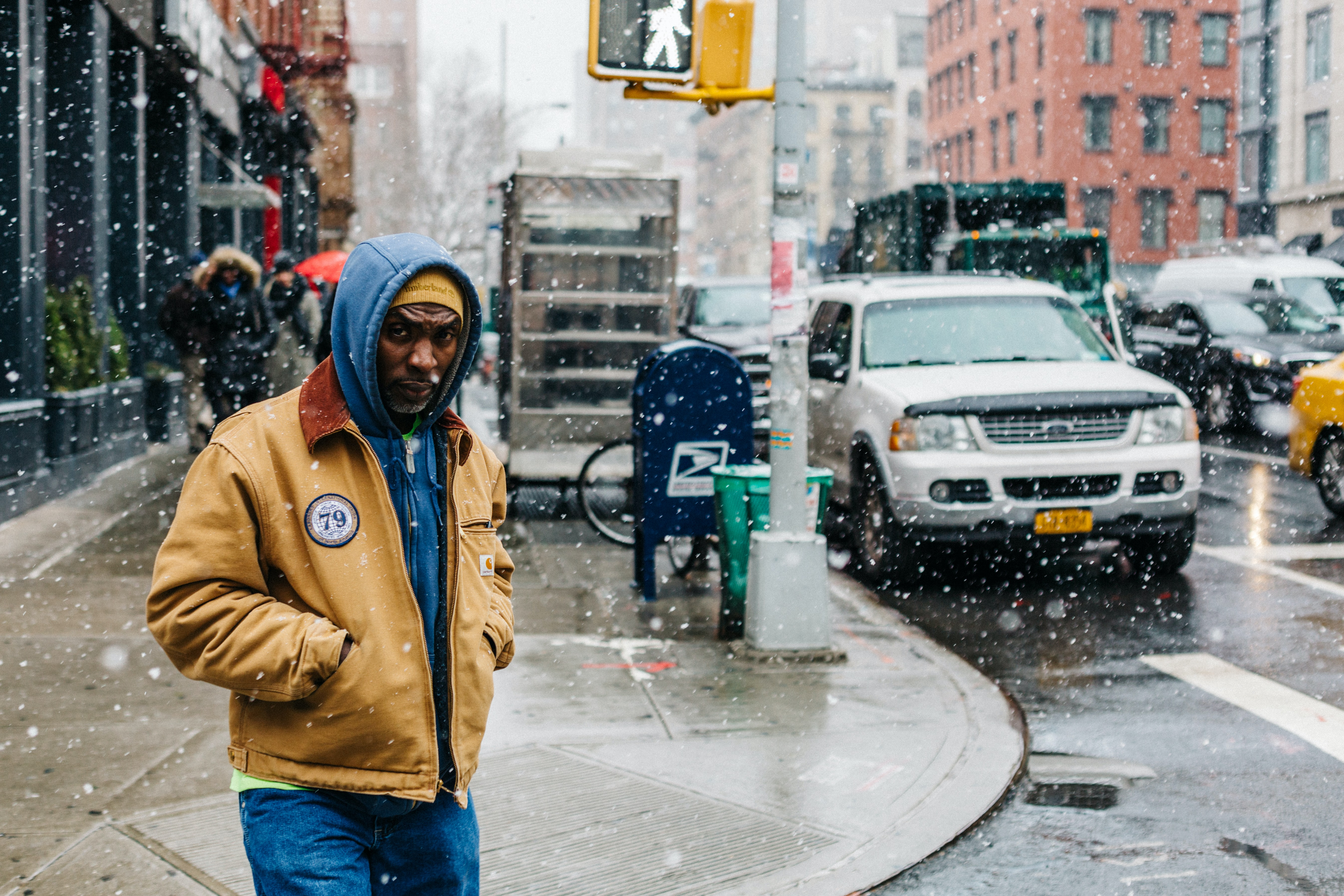 A man in a hoodie in the streets of New York on a snowy day