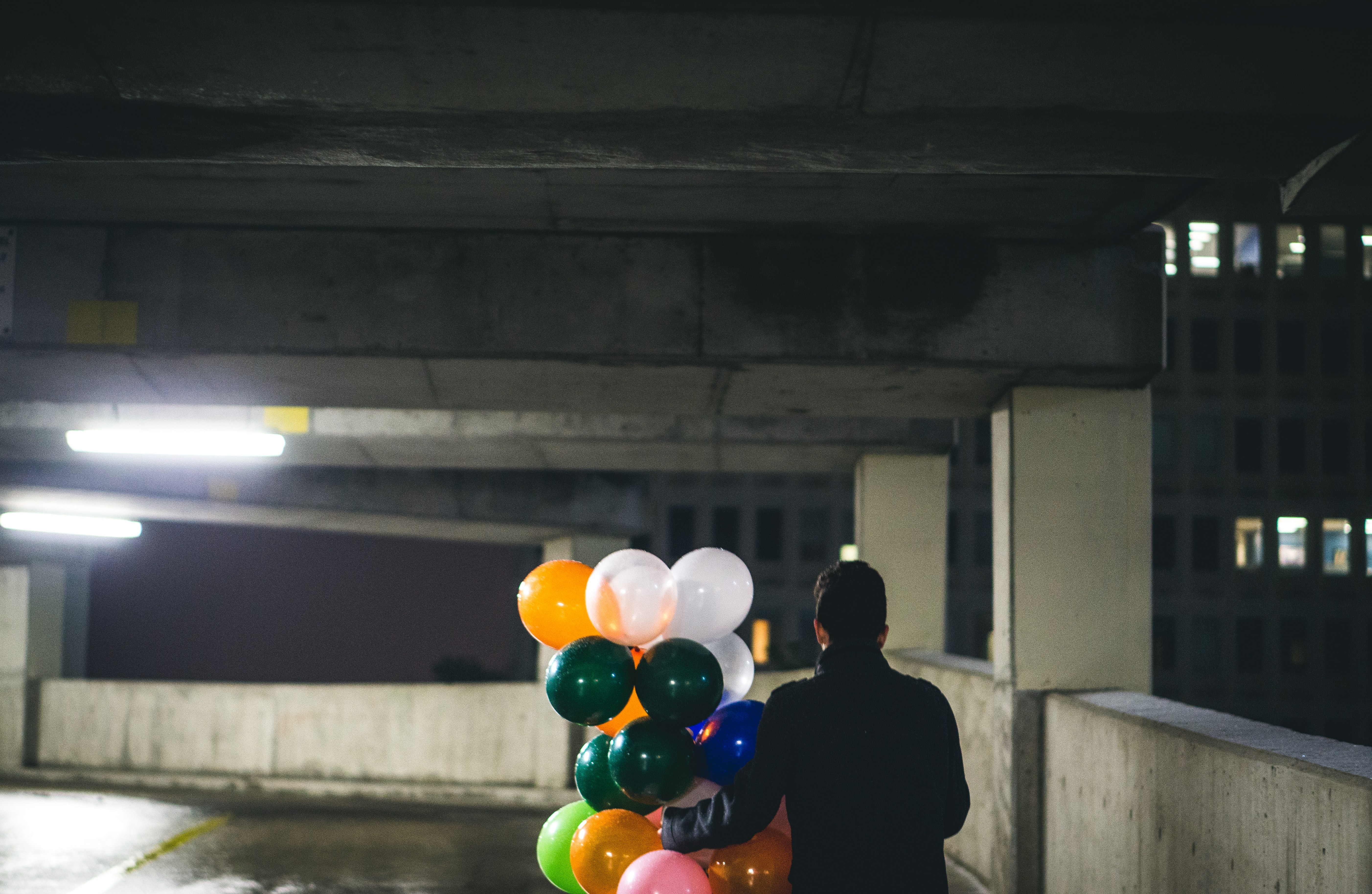 Person carrying colorful birthday balloons through a dark parking lot