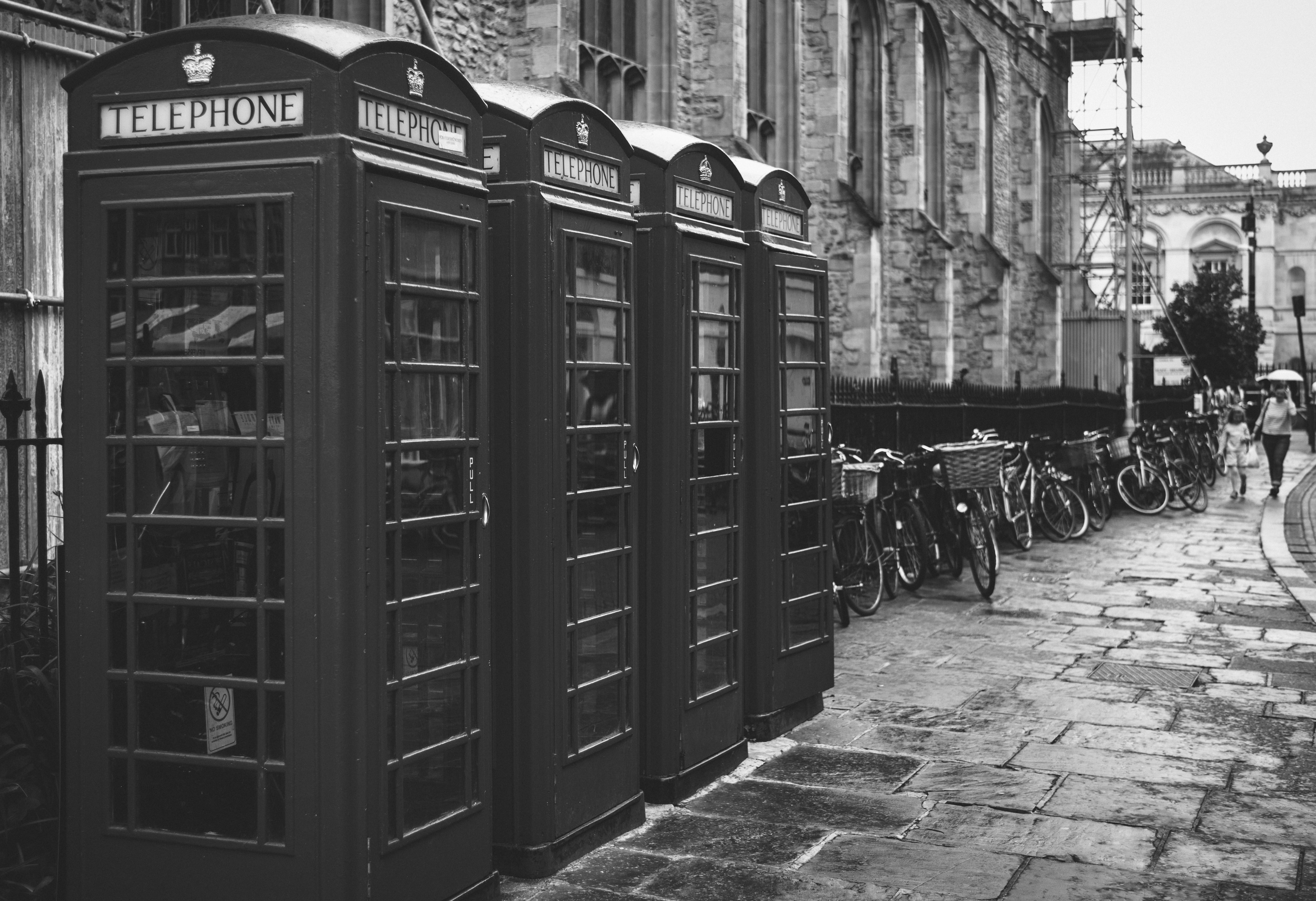 Black and white shot of traditional red telephone boxes on street with bikes in Cambridge
