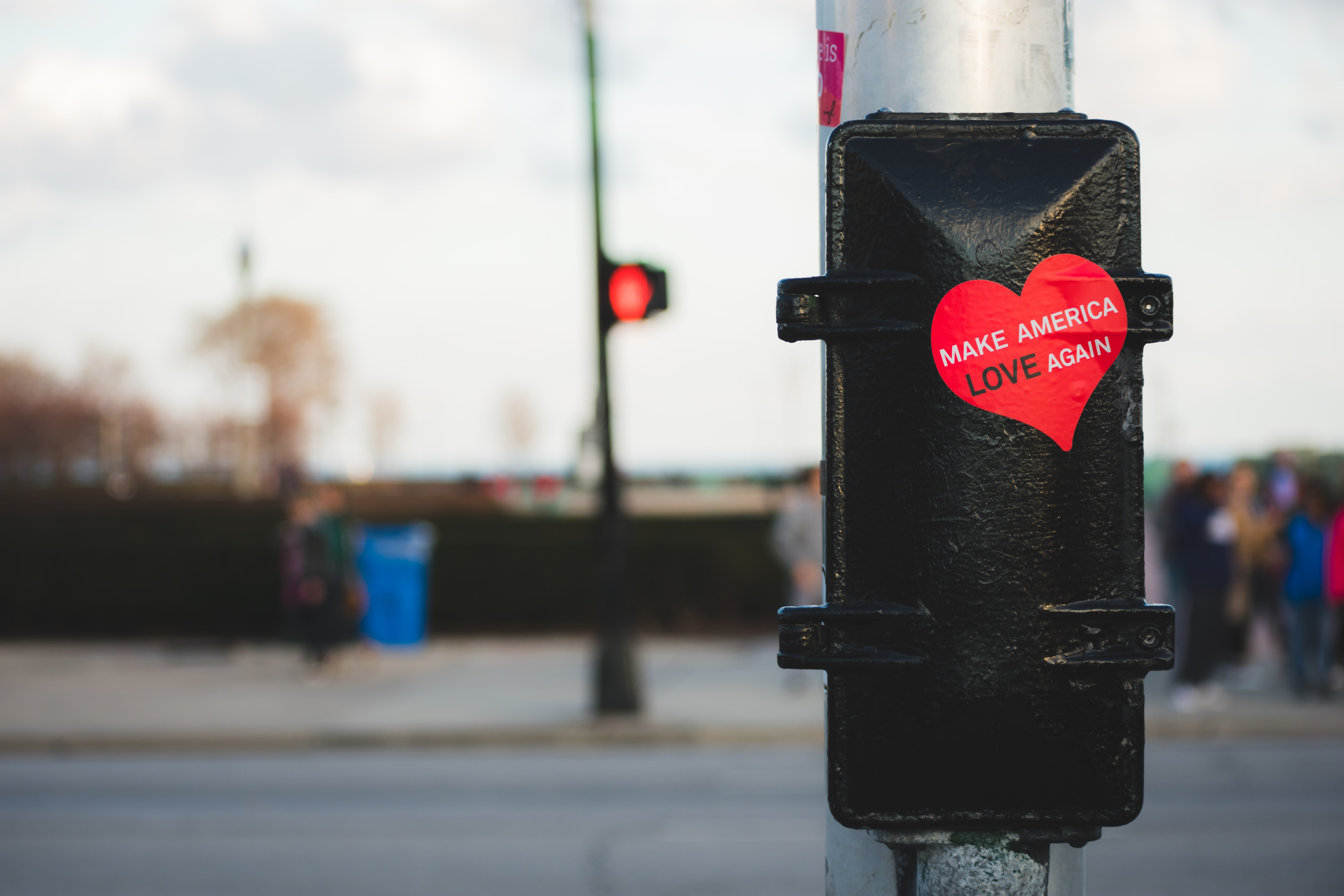 "A red, heart-shaped sticker on a traffic post reads ""Make America Love Again."""