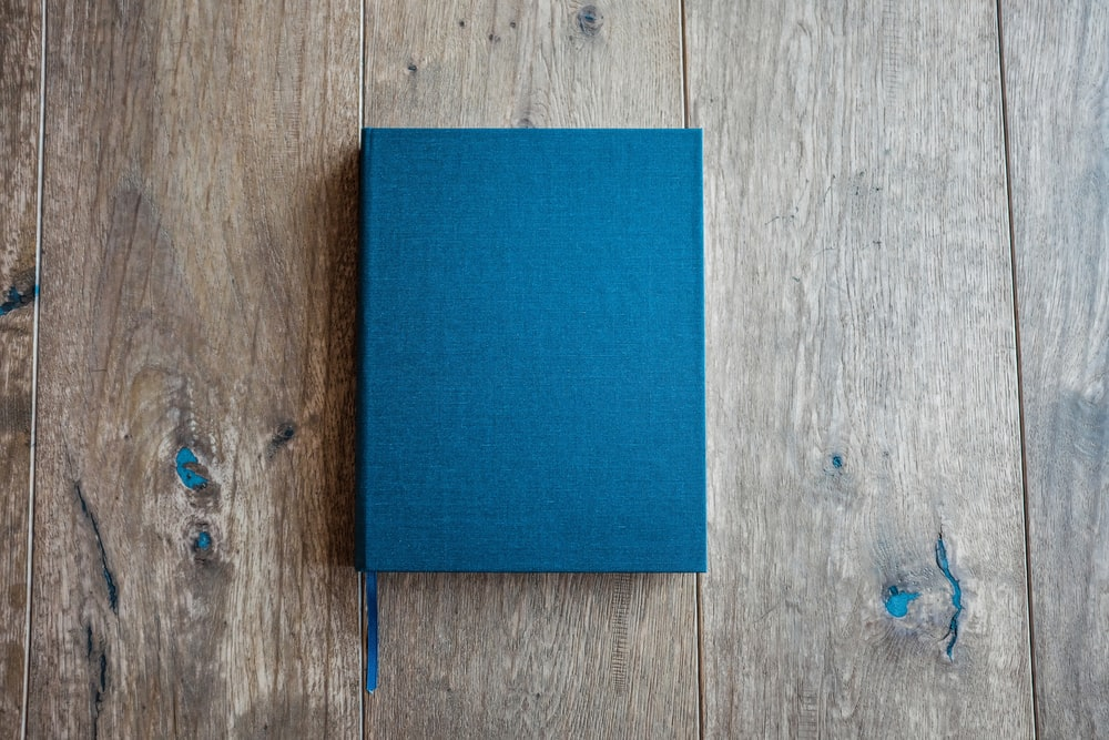 blue book on brown wooden board
