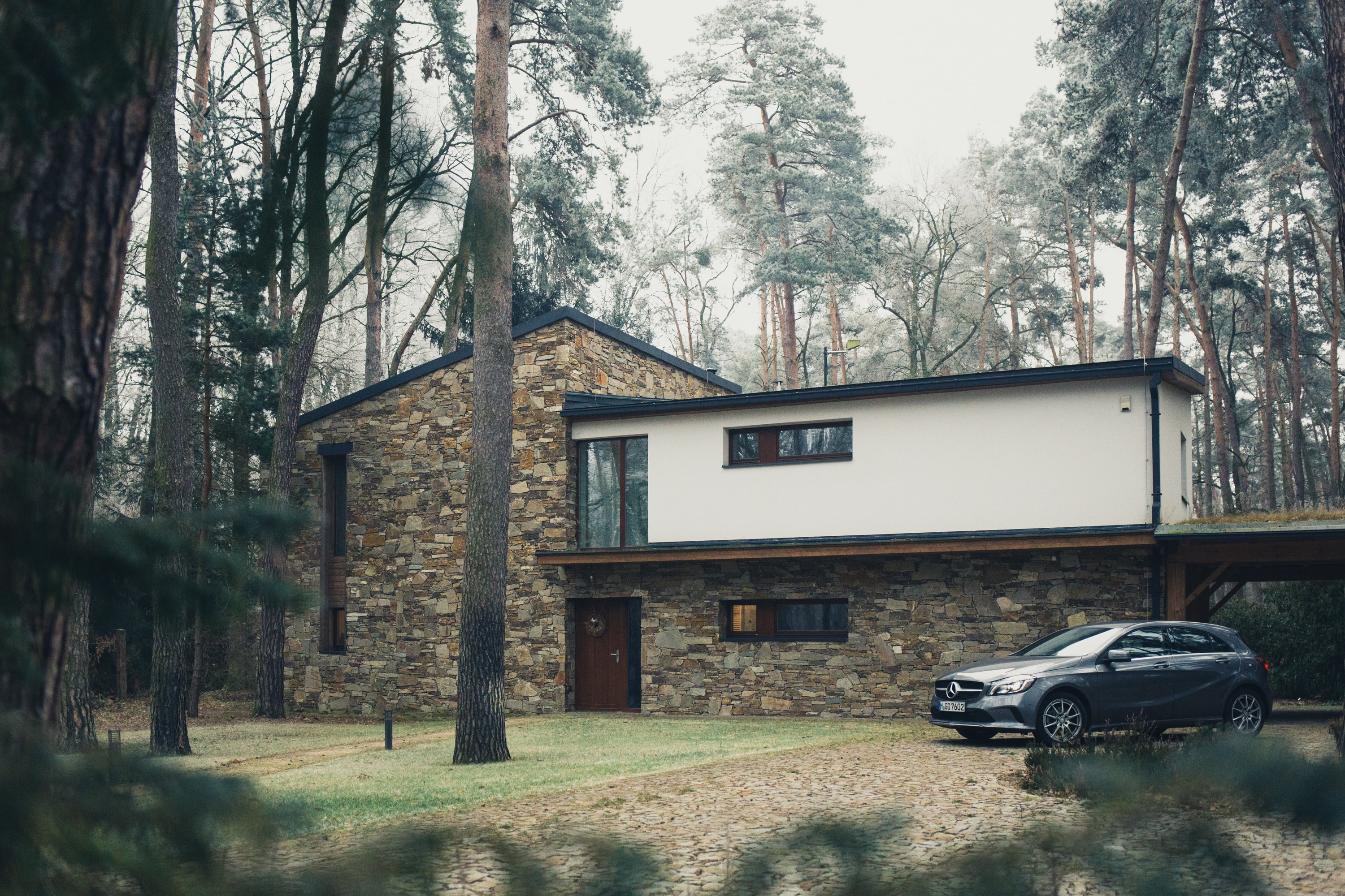 Modern brown and white house in the middle of pine tree forest with car parked in driveway