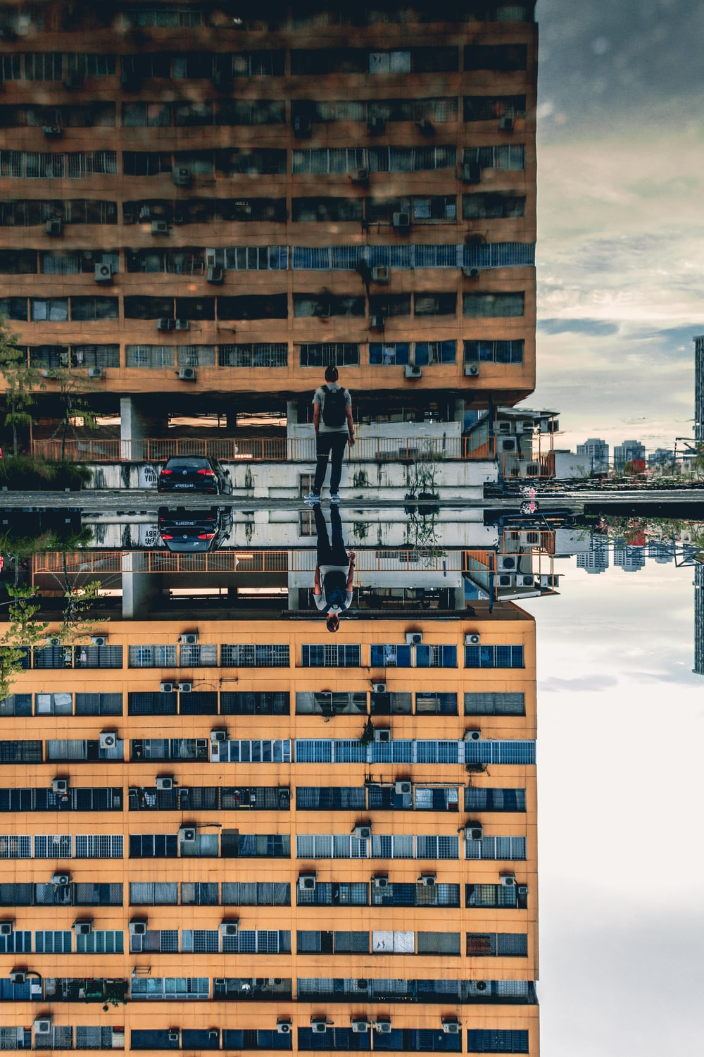 man standing in front of brown concrete high-rise building during daytime