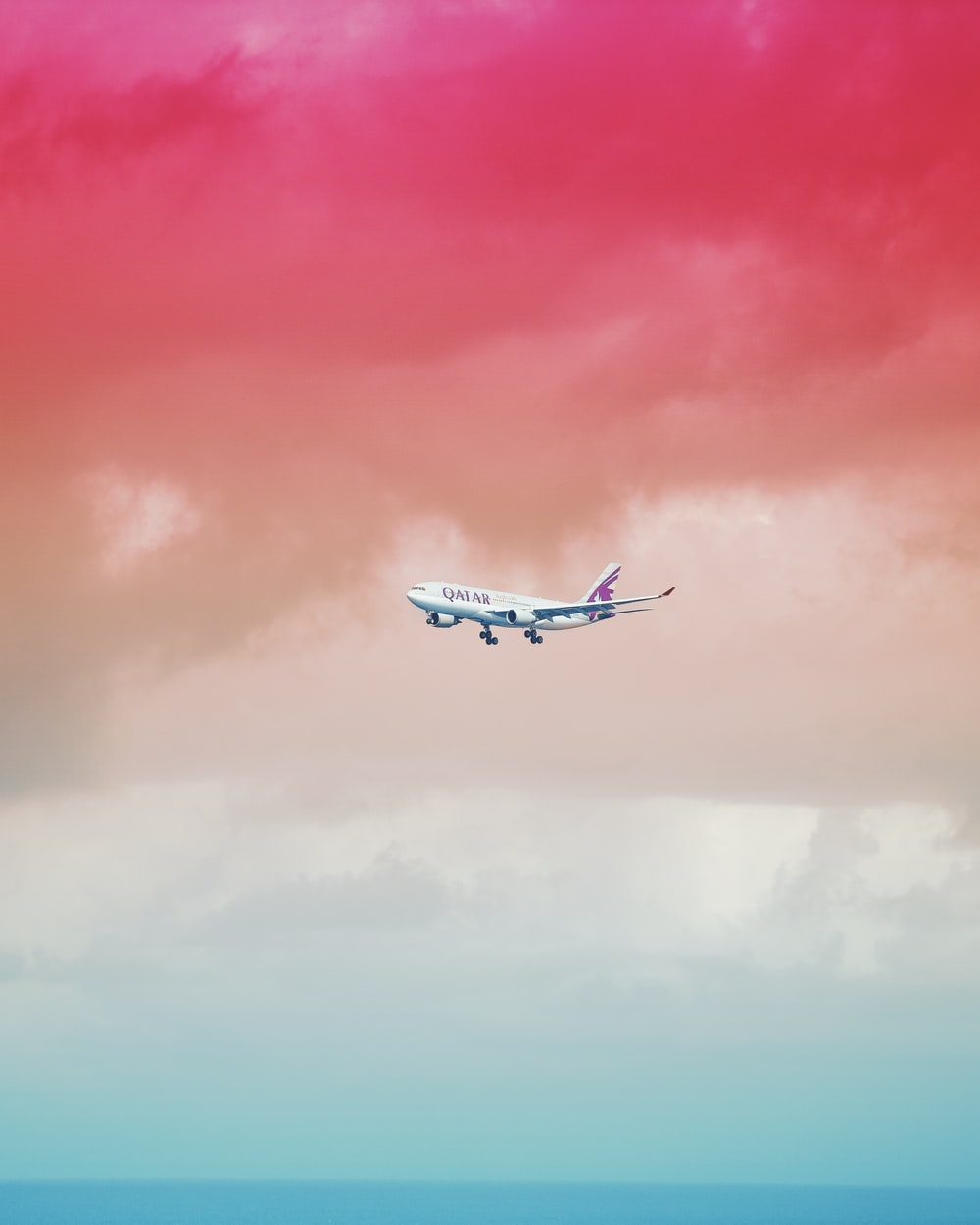 Qatar Airlines airplane flying under red cloud formation