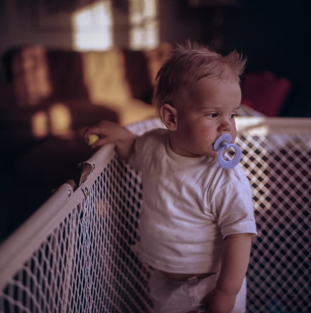 baby with purple pacifier standing on crib