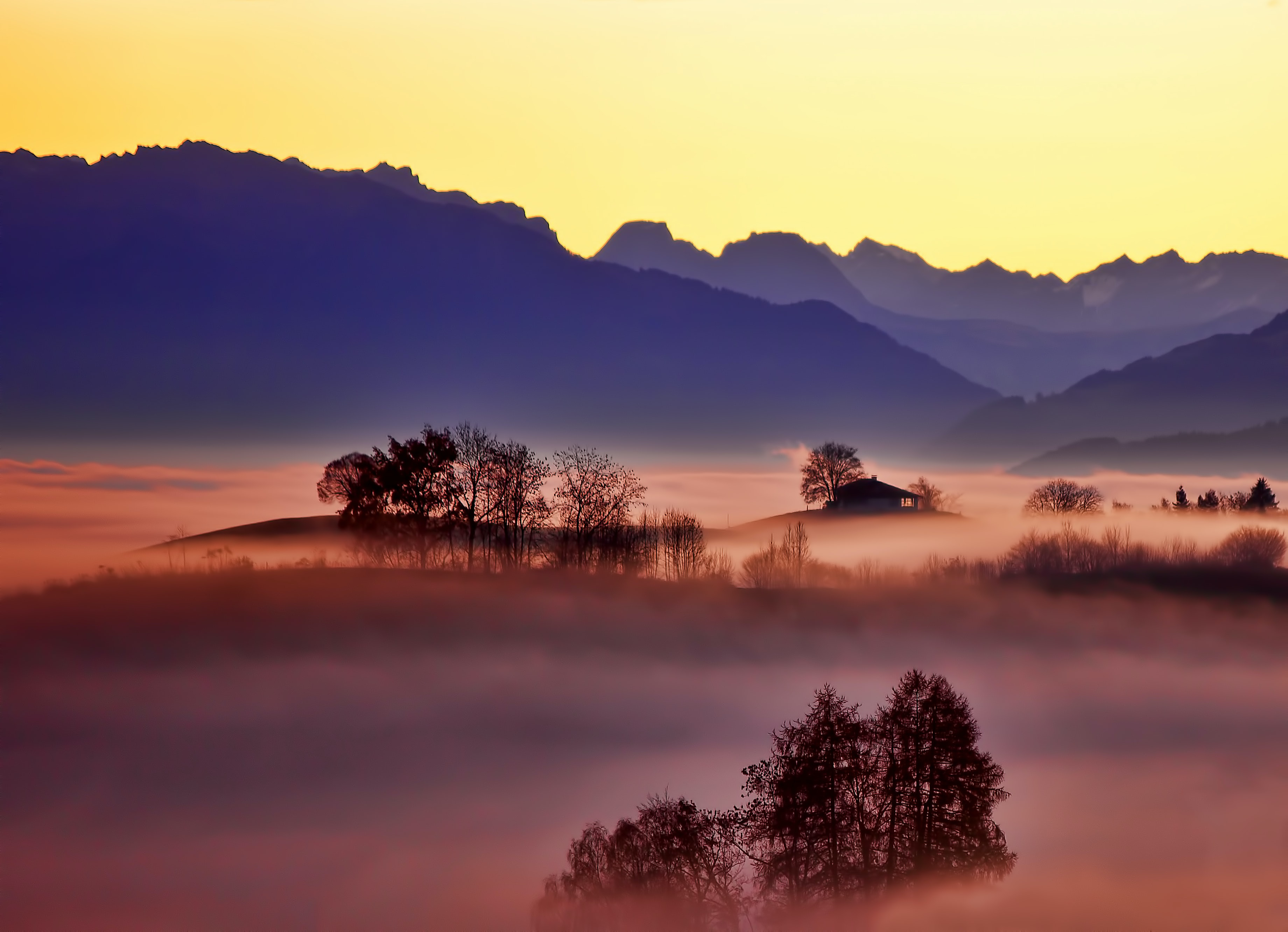 Colorful mountain scene covered in mist during the sunrise