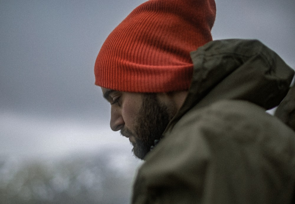 man wearing gray hoodie and orange knit cap