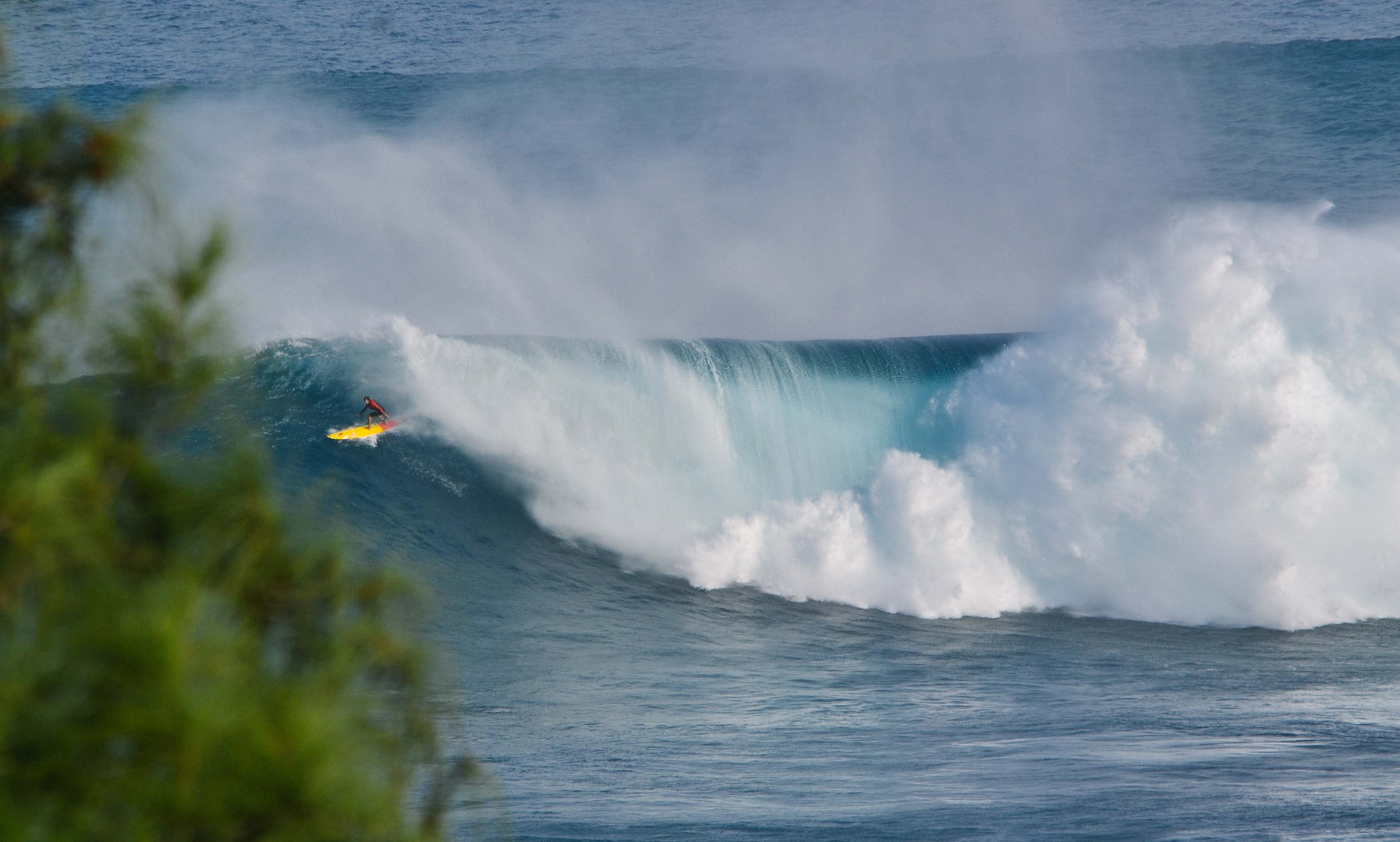 A person surfing on a yellow surfboard, catching a massive wave in Jaws