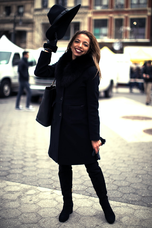 woman wearing black coat standing on gray concrete pavement