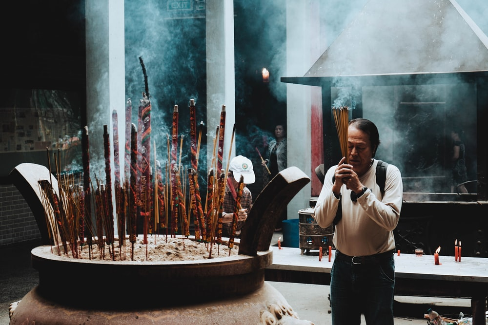 man in beige long-sleeved shirt in praying gesture