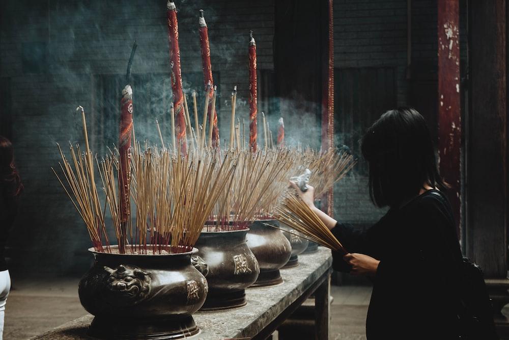 woman putting incense sticks on pot