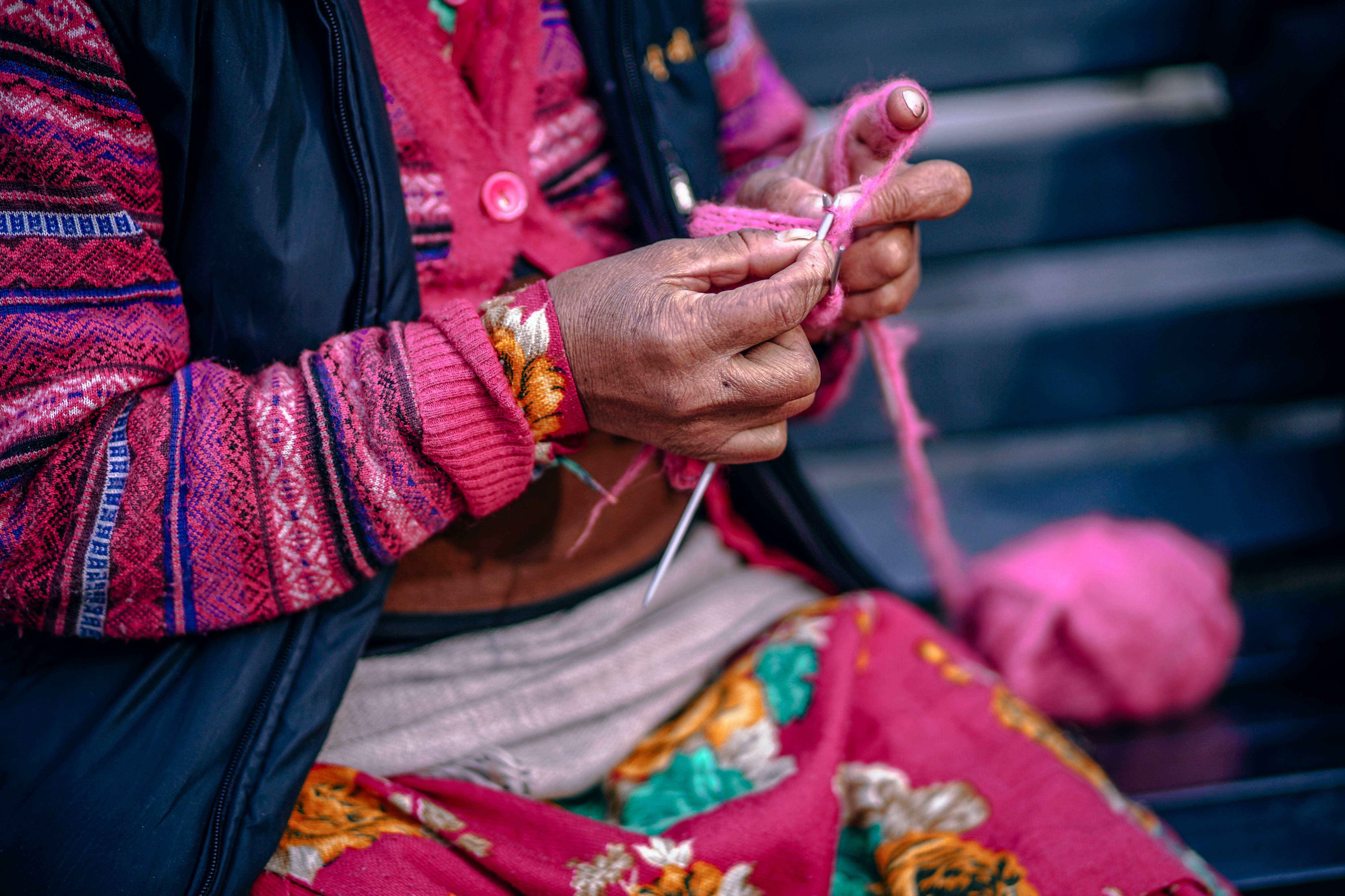 A person wearing a lot of pink clothing knitting with pink yarn in Manali