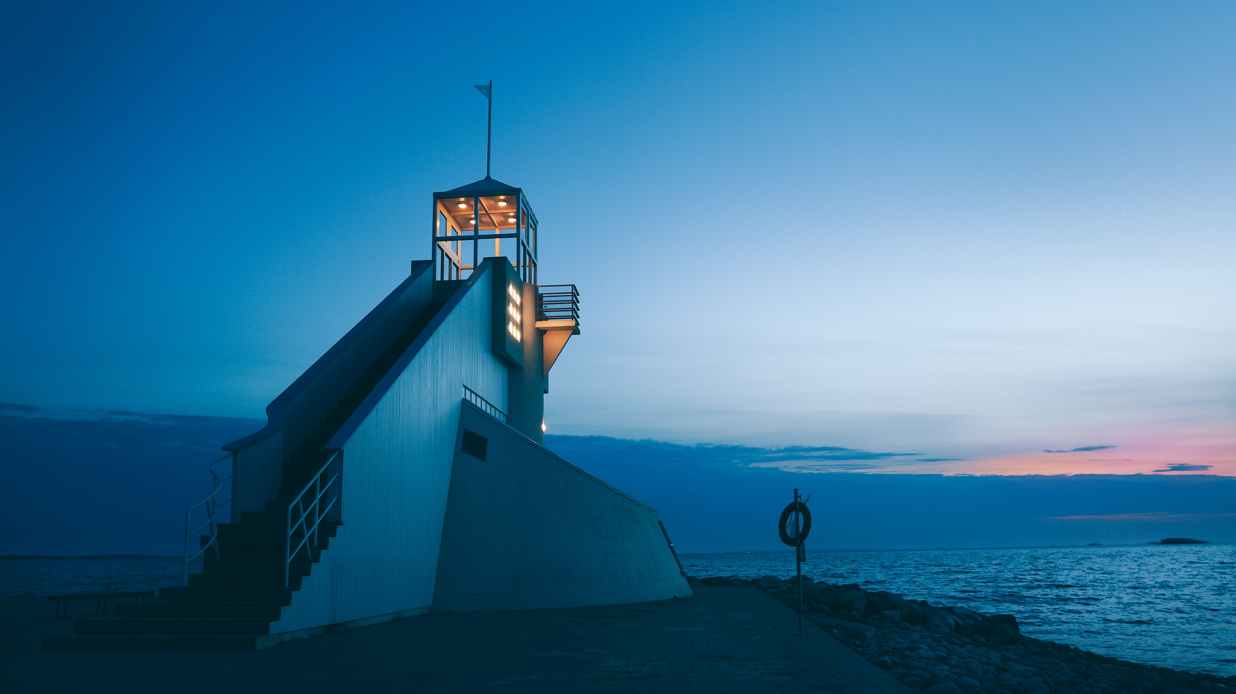 A lighthouse beacon with illuminated lights in front of a blue sky and sea at sunset, Oulu