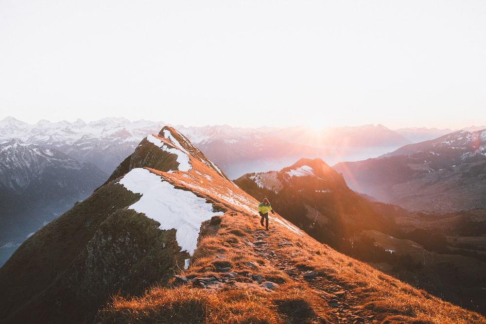 A person walking on a rocky path along the mountain ridge