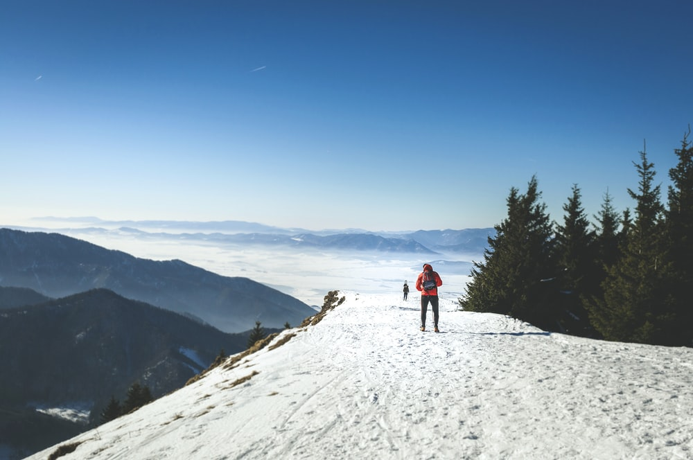 person standing on top of mountain covered by snow