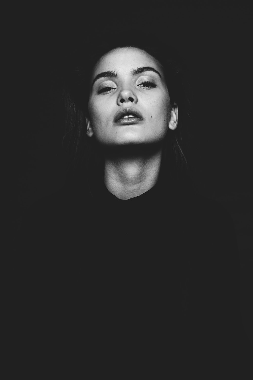 black and white photo of woman looking upward