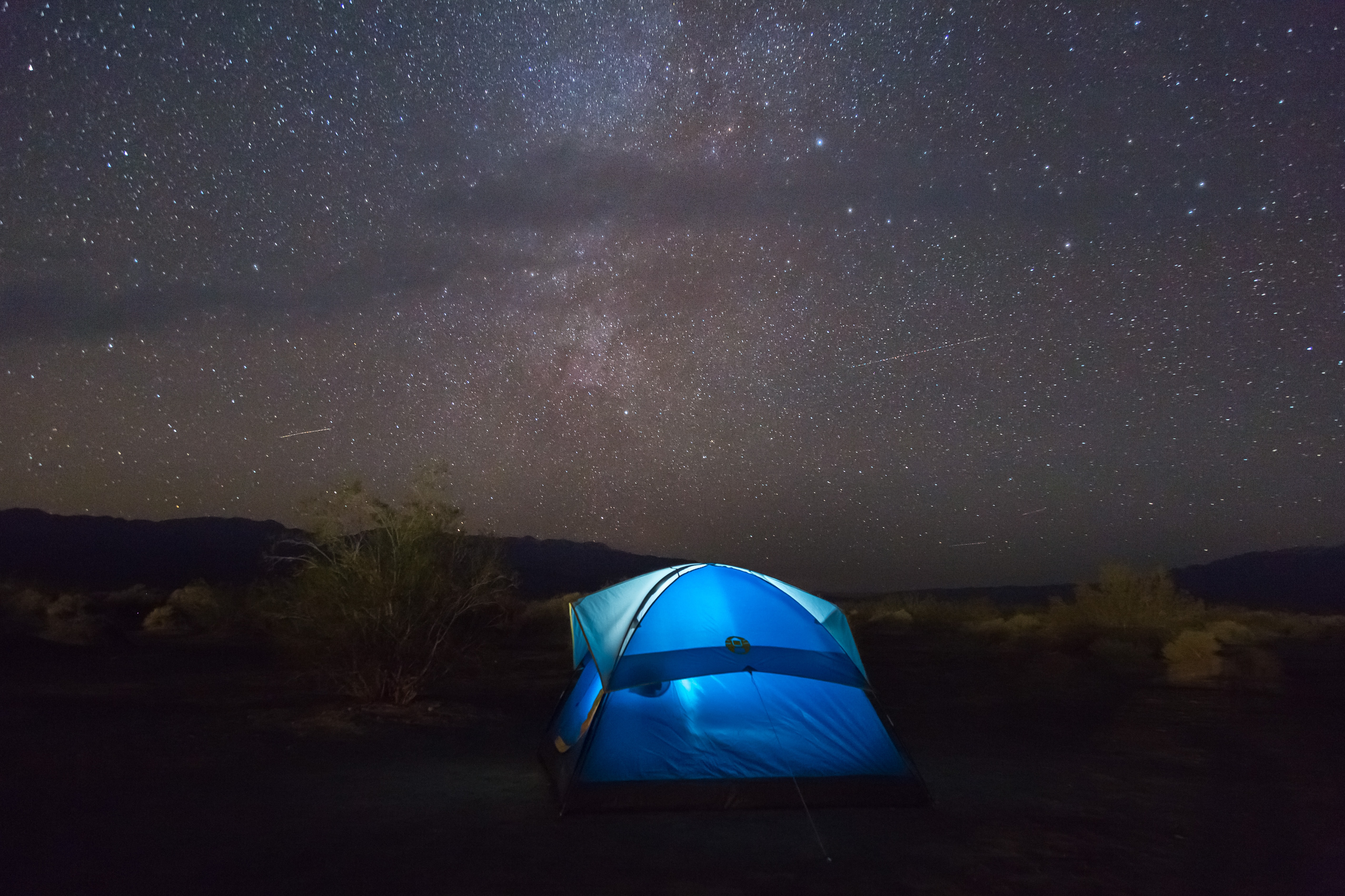 Blue tents glows in against a dark starry night sky
