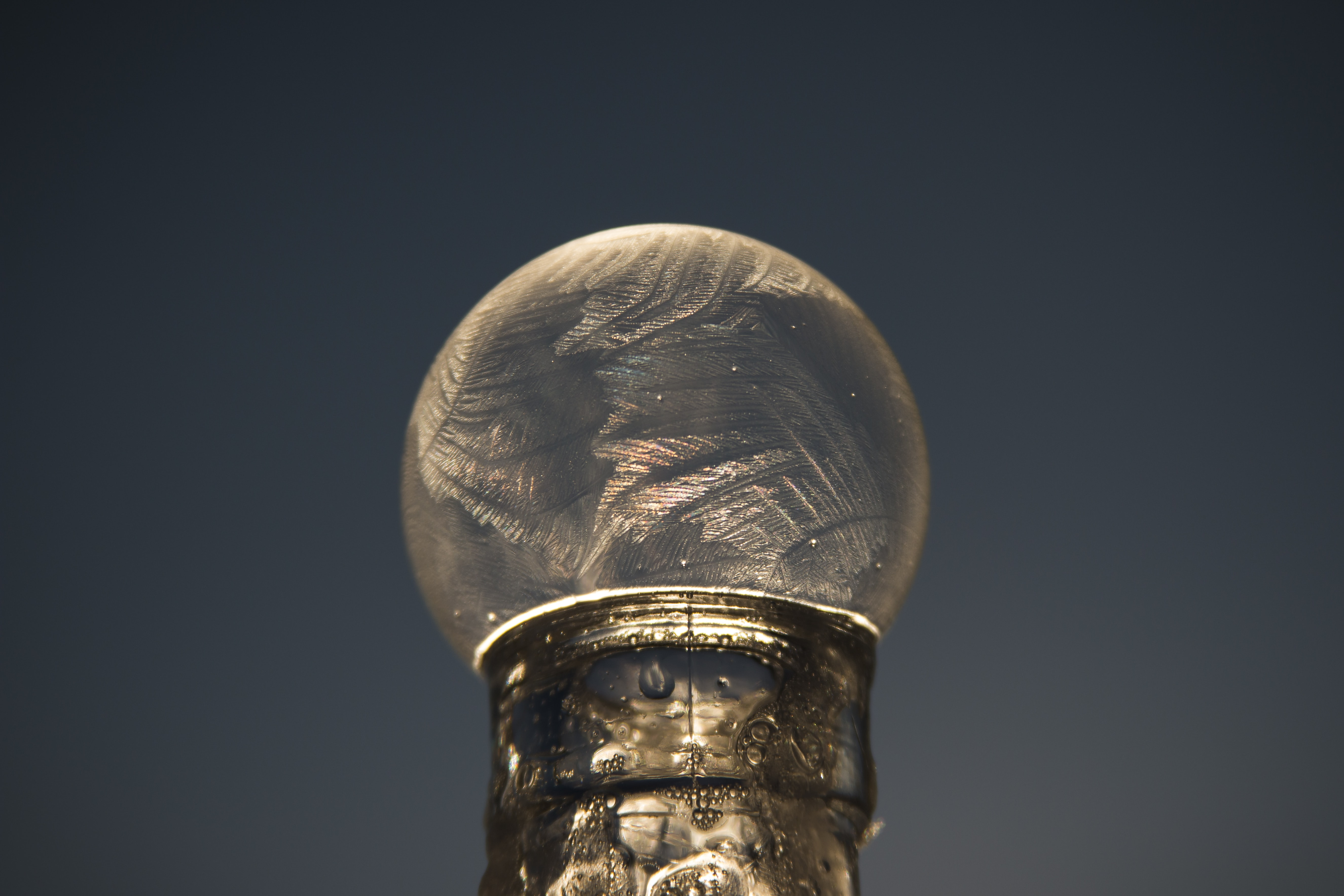 Close-up of a frozen bubble atop a bottle at Billings, Montana, seen against a clear sky