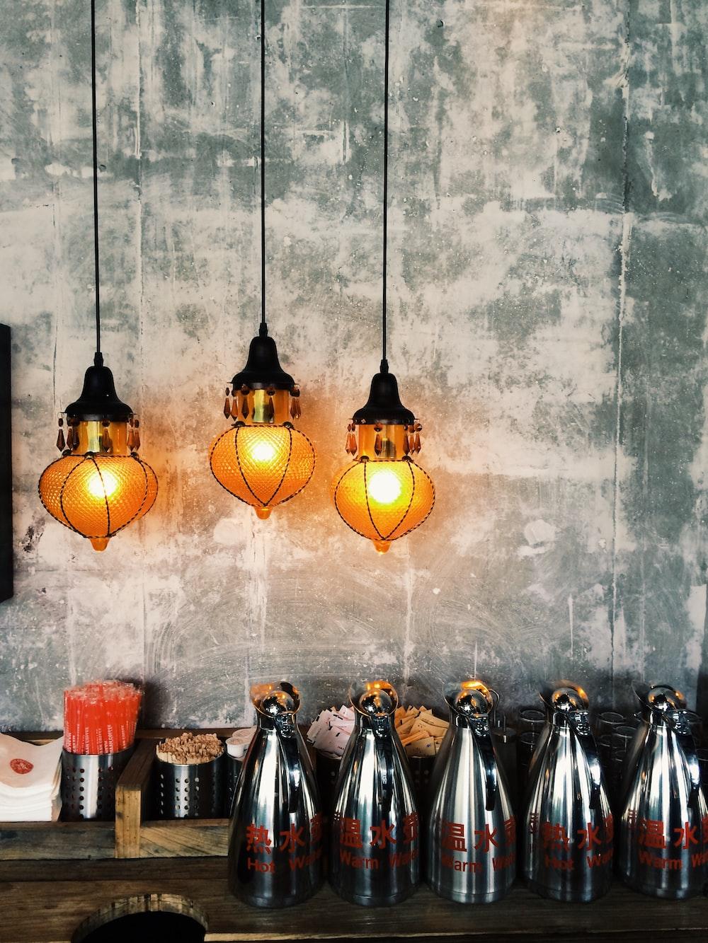 three brown pendant lamps near wall