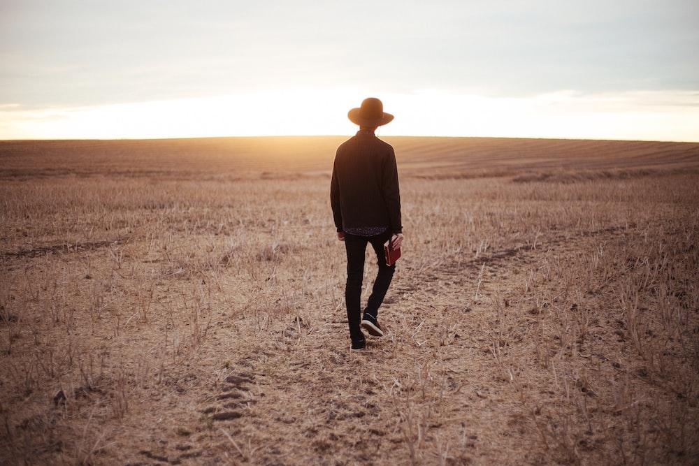 man walking on dried plain while looking towards the sun on horizon