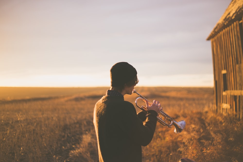 man playing trumpet outside house on field during daytime
