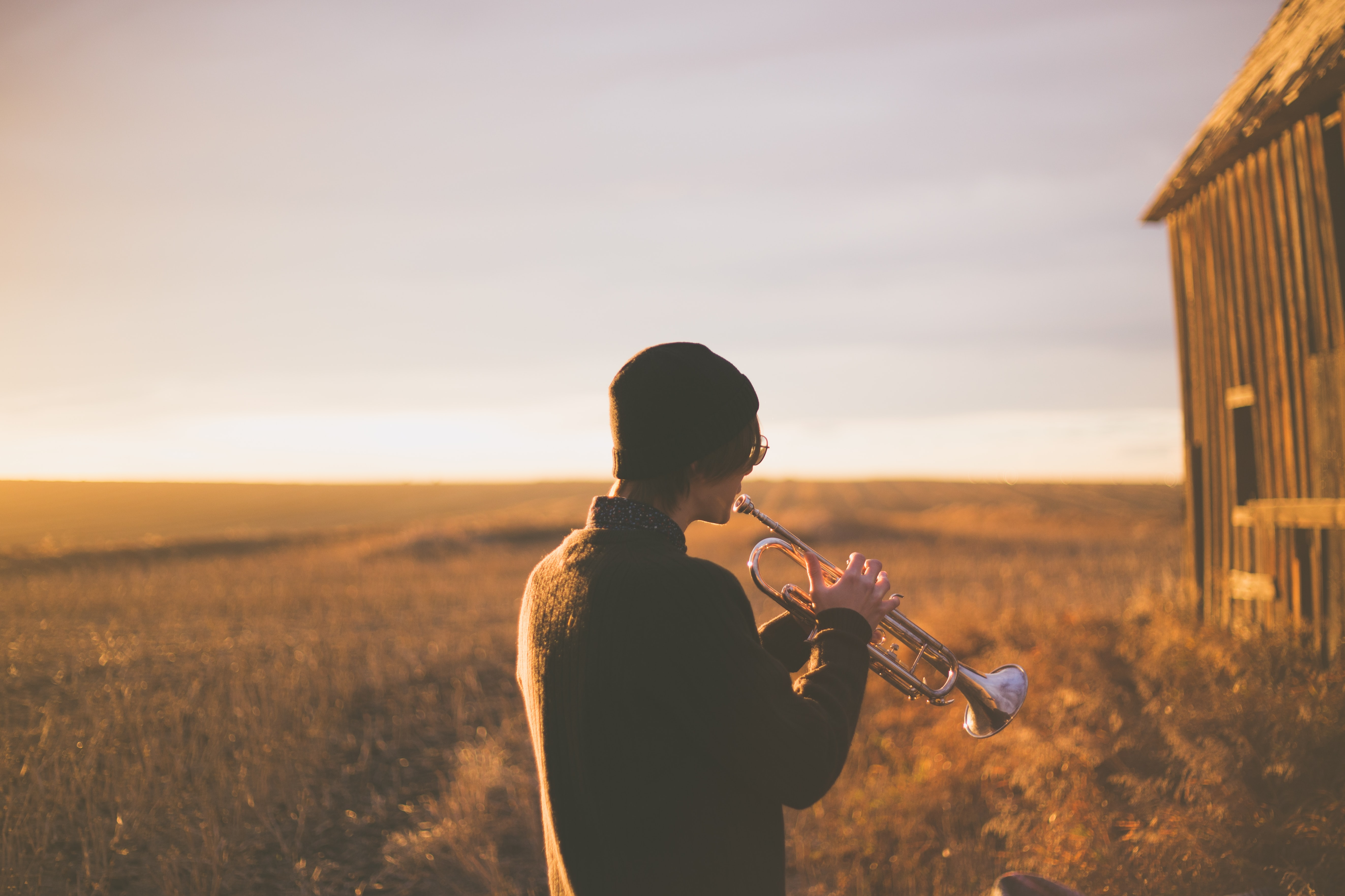 Musician playing trumpet alone in an empty forest field