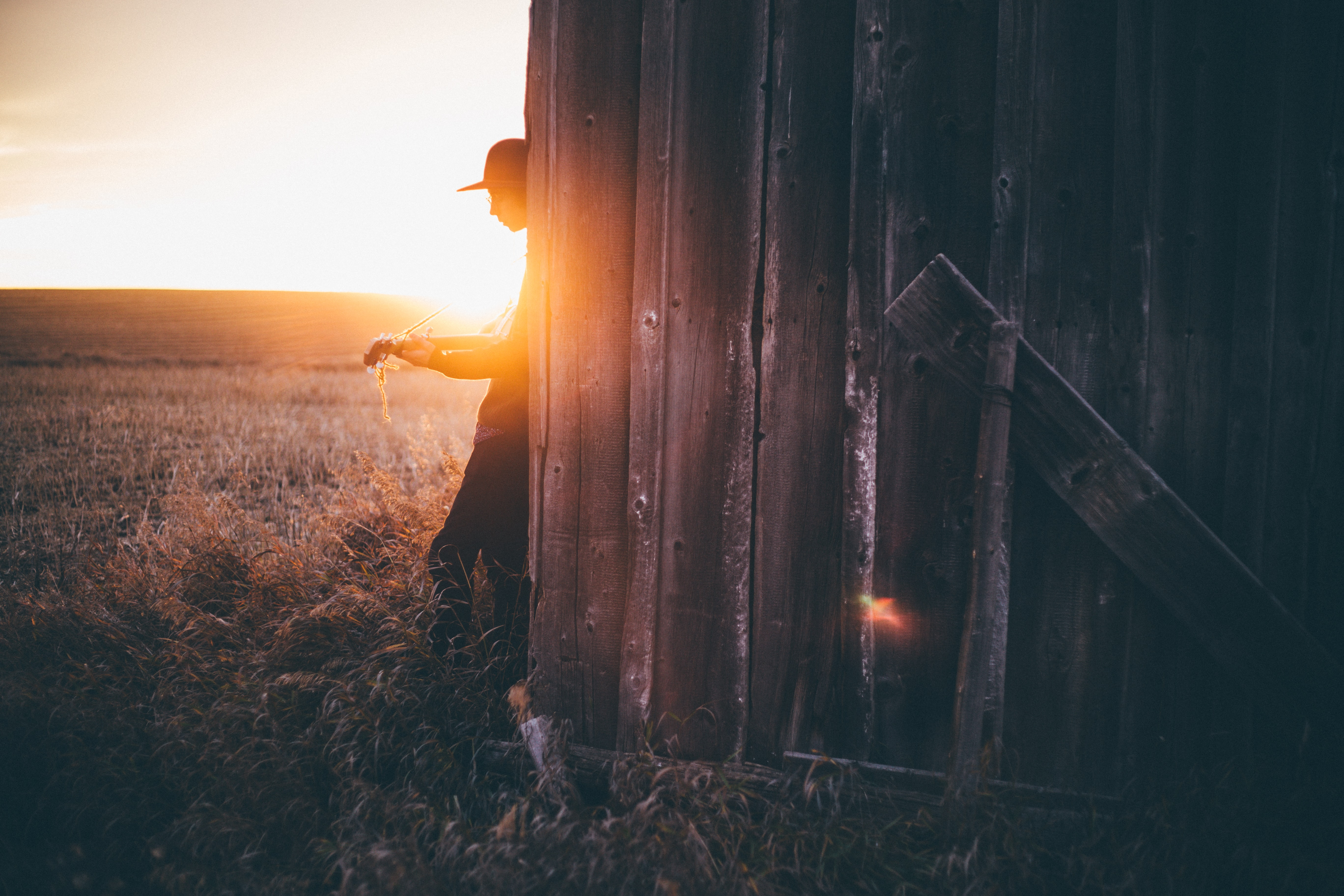 silhouette of man leaning on gray wooden house during sunset