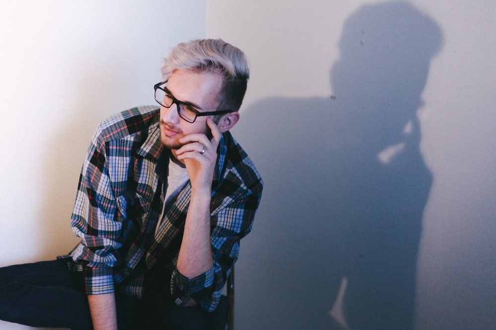 man wearing black, blue, and red plaid collared button-up long-sleeved shirt and eyeglasses sitting and putting left hand on his face