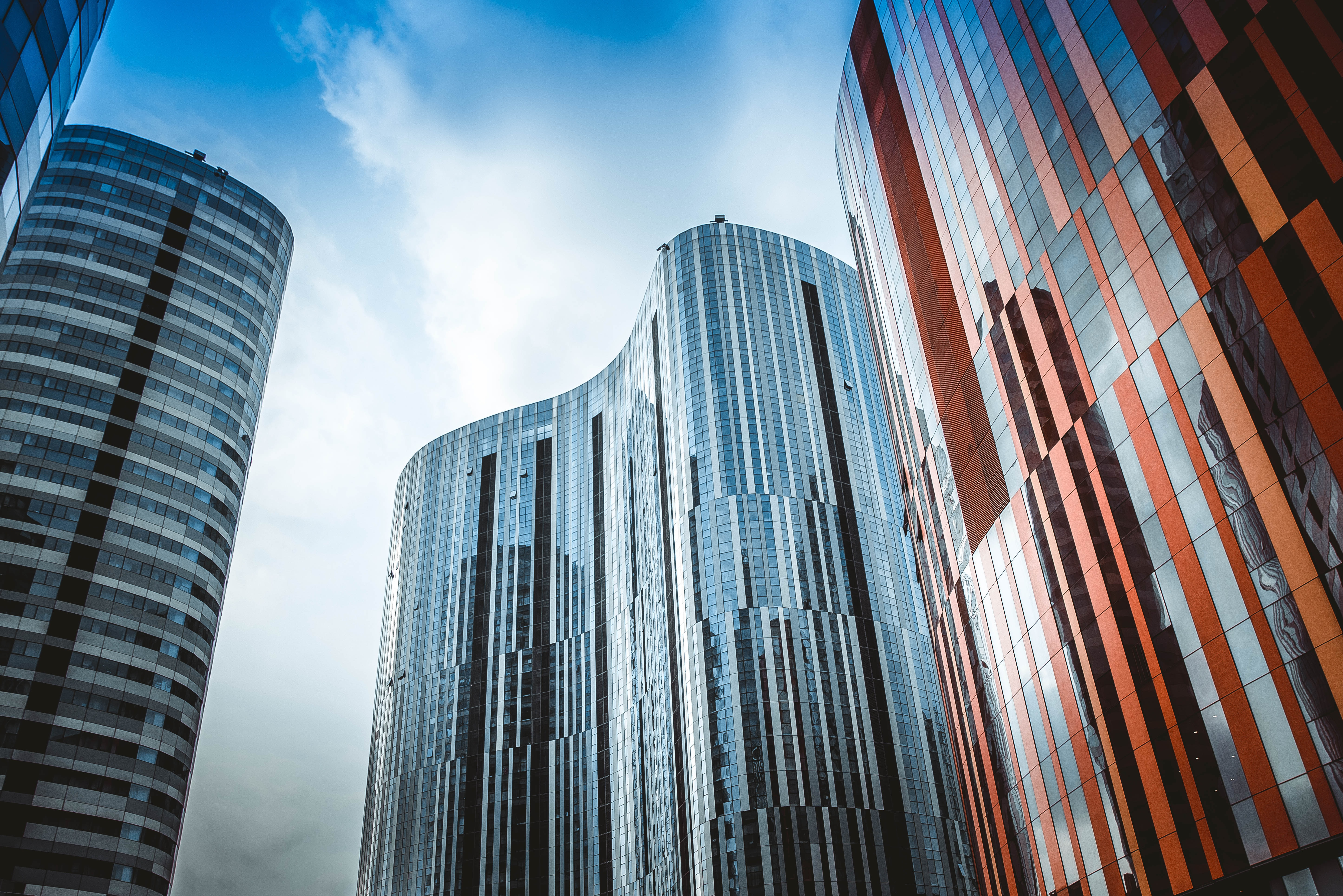 Several buildings with curved architecture, and reflective surfaces in soft light.