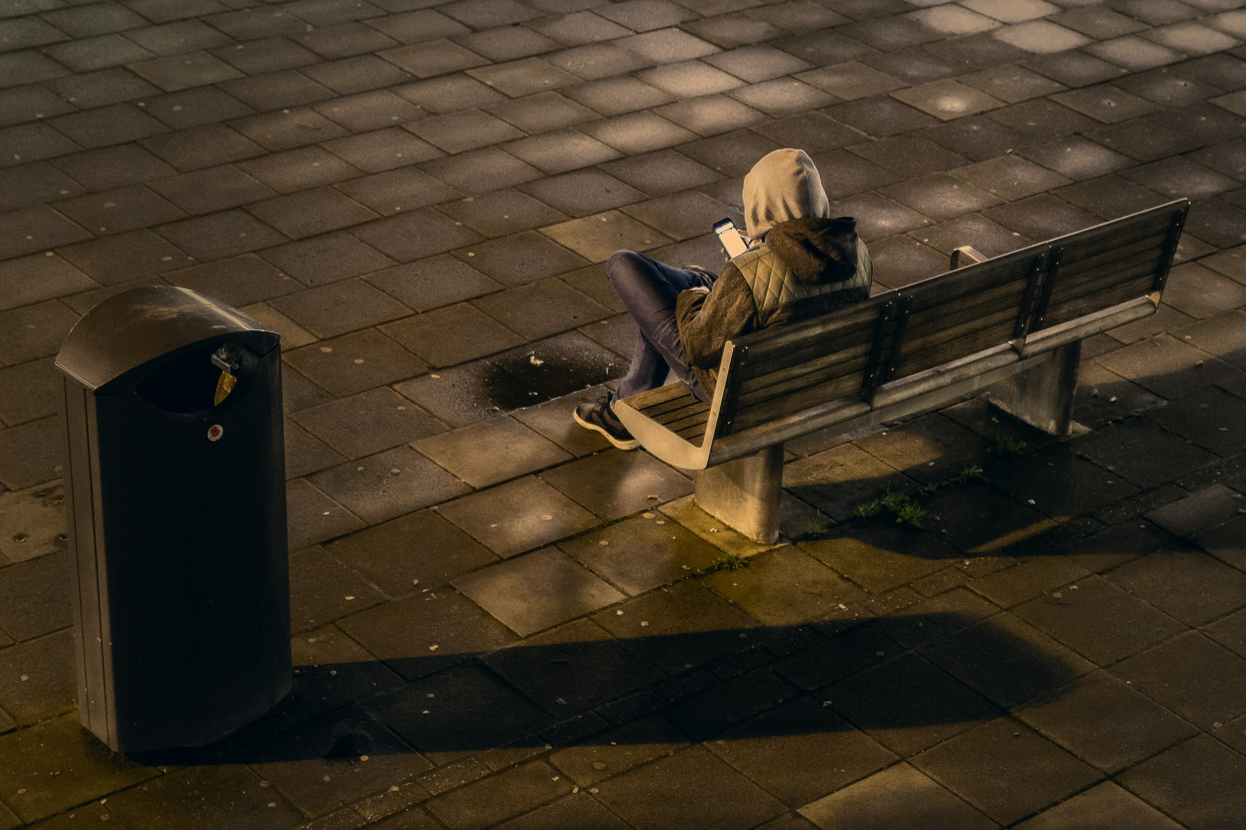 A hooded man on a bench using his smart phone beside a garbage can in a tile floor outside at night