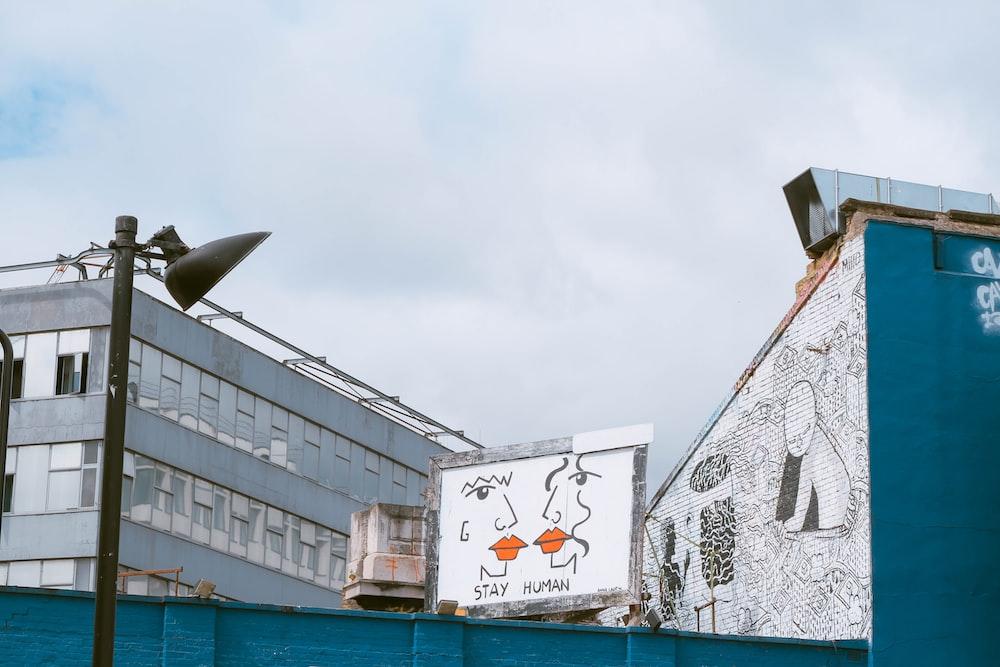 white and grey wooden billboard near white concrete building