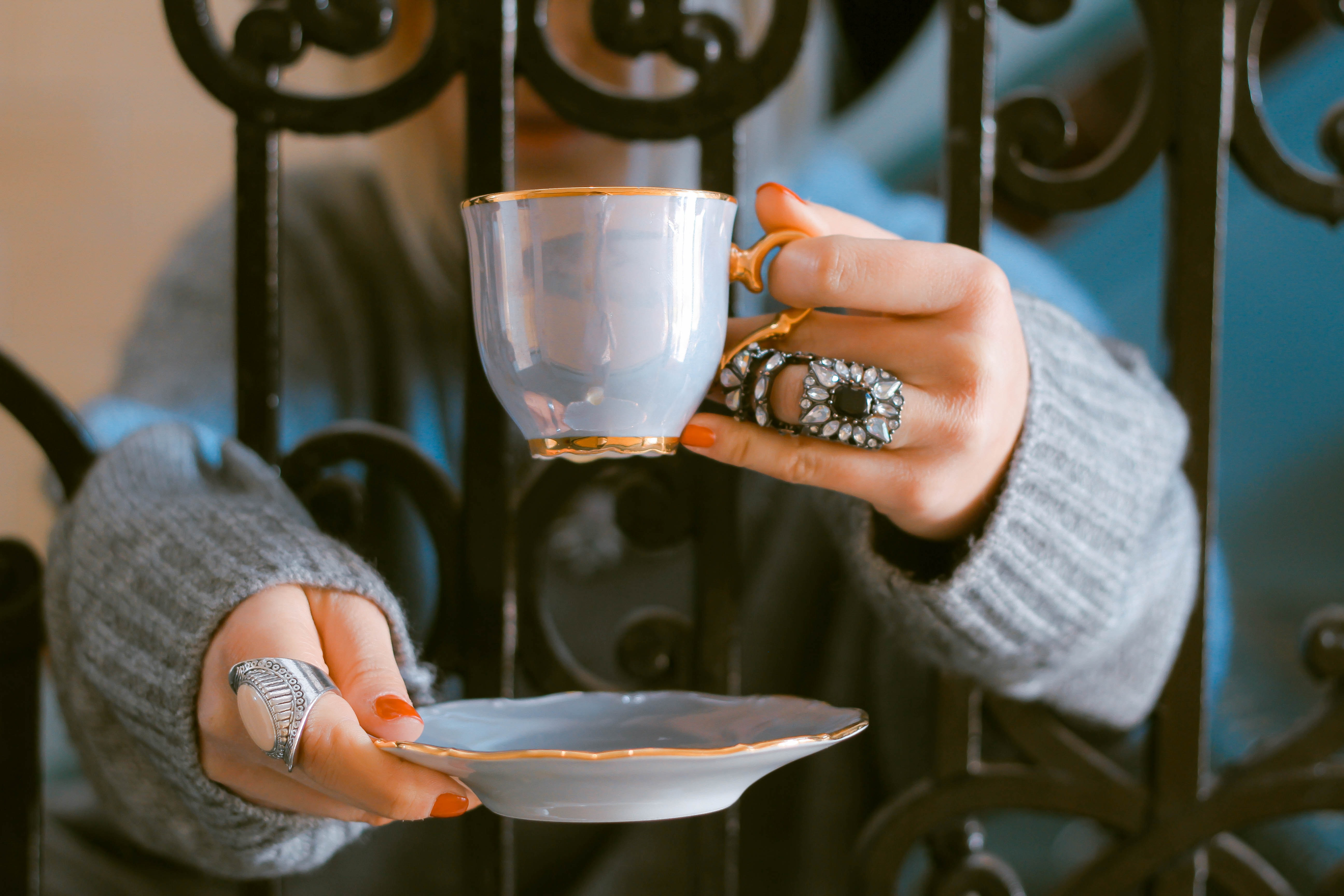 A woman wearing a grey oversized sweater and rings holding a blue ceramic cup and saucer while leaning on a gate in London