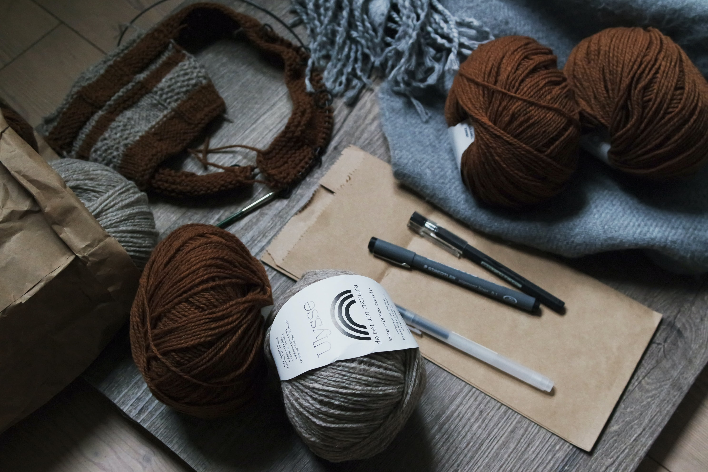 Yarn, a knitted hat, a brown paper bag, and a notebook and pens in Milan